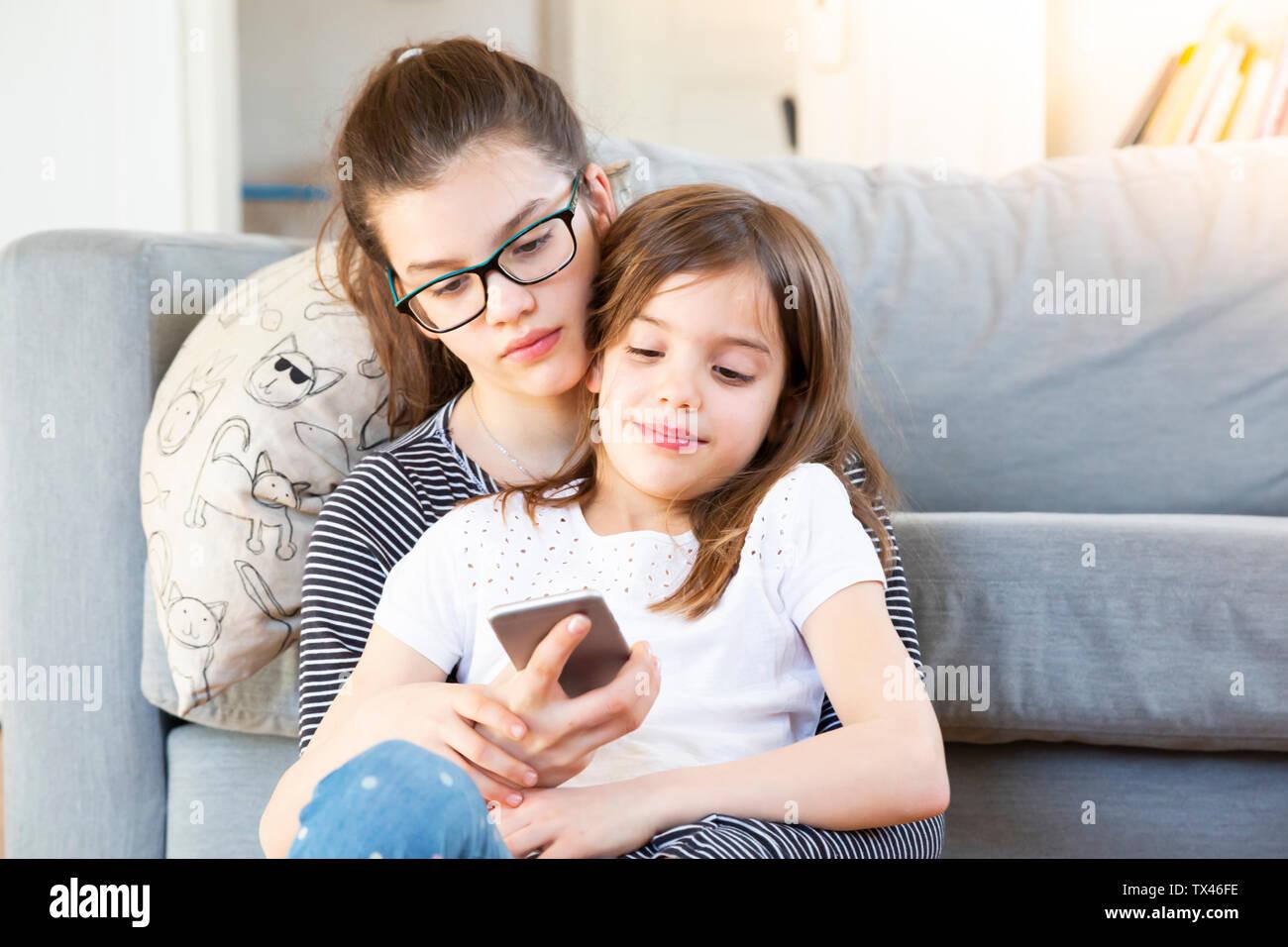 Deux soeurs assis en face de la table looking at smartphone Banque D'Images