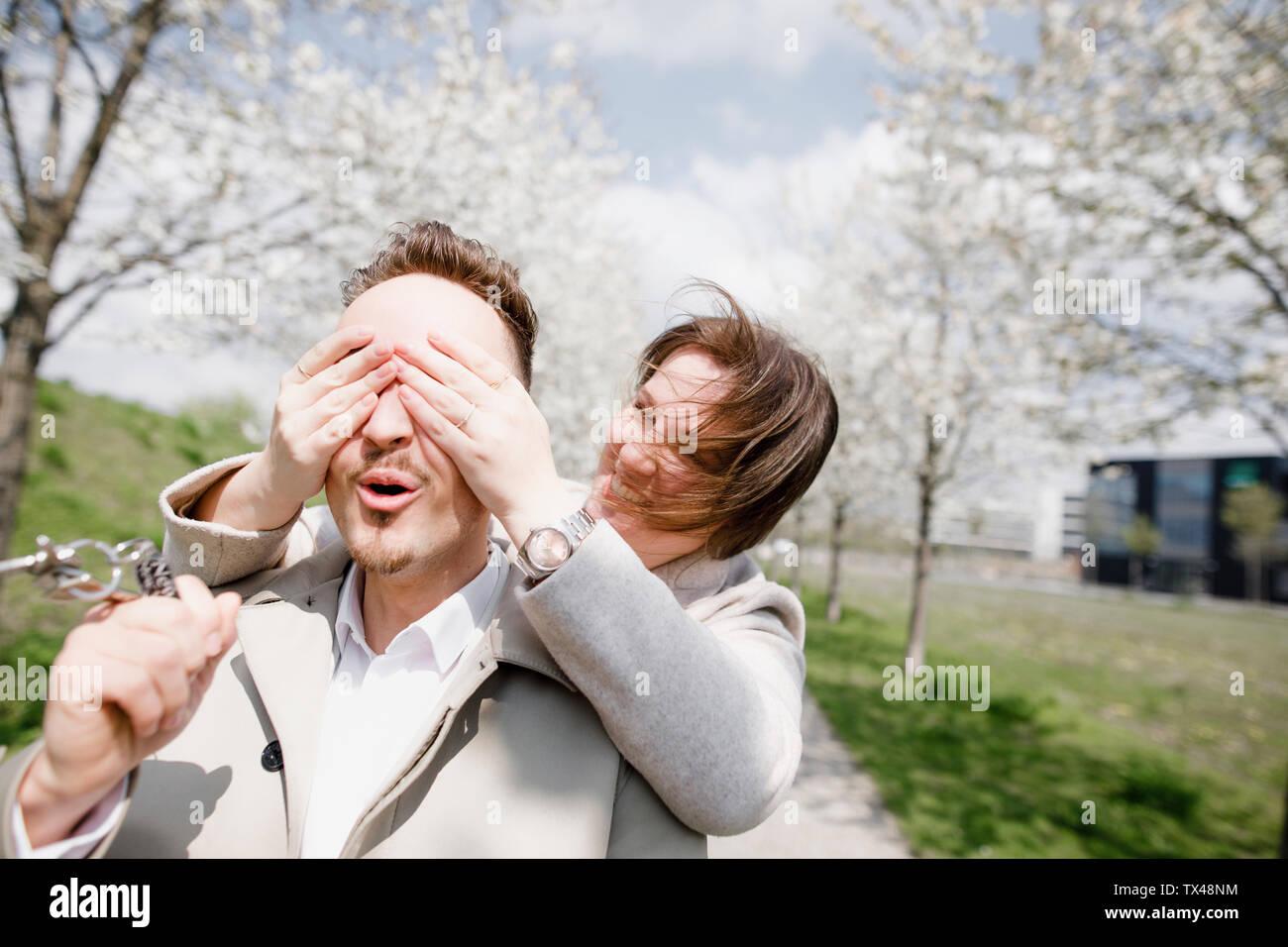 Happy young man holding latchkeys pour nouvelle maison, tandis que la femme est couvrant ses yeux Banque D'Images