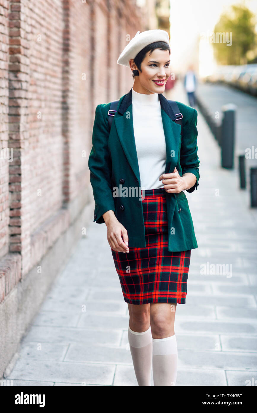 Jeune femme à la mode marche le long d'un mur de briques dans la ville Banque D'Images