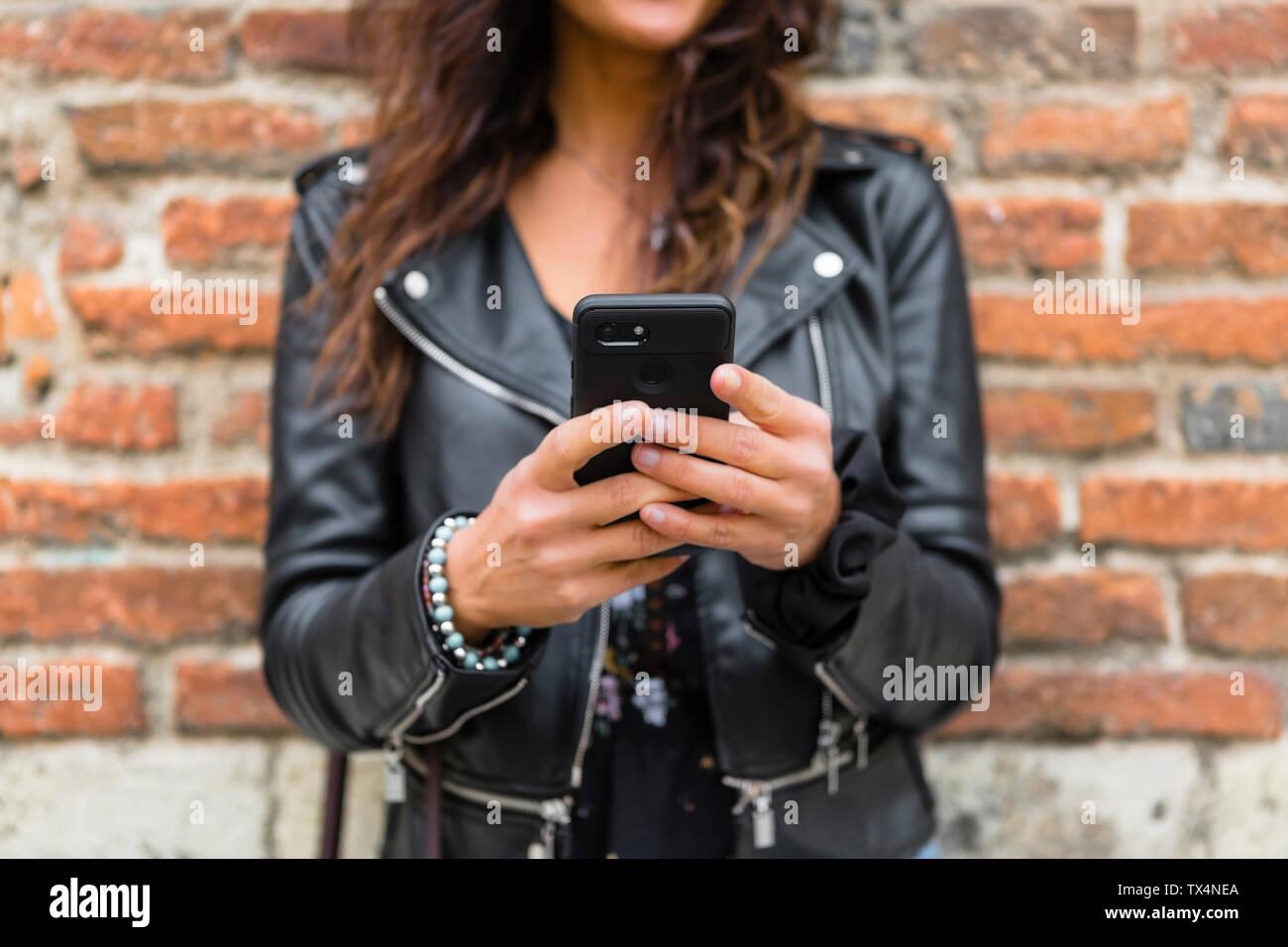 Jeune femme portant veste en cuir noire, en utilisant smartphone, mur de brique à l'arrière-plan Banque D'Images