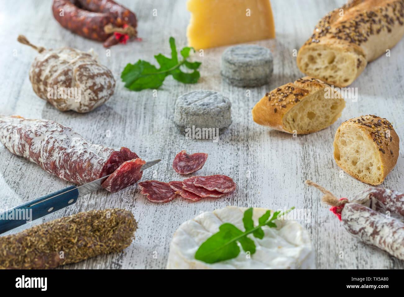 Des collations avec du vin français - divers types de fromages, pain , les saucissons secs, charcuterie, vigne rouge sur un fond gris. Vue d'en haut. Arrière-plan de l'alimentation Banque D'Images