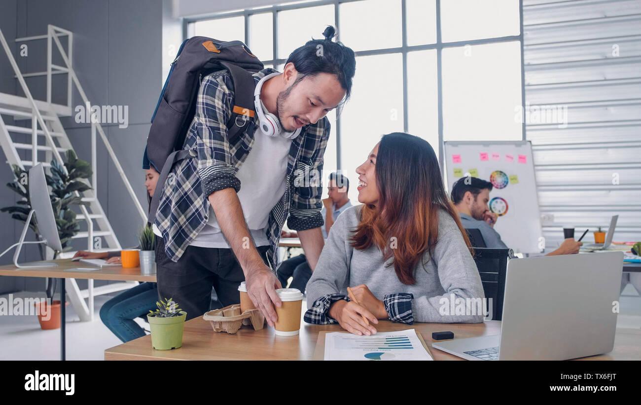 Creative designer homme acheter tasse à café femme collègue au bureau moderne en matin à 24.vie de travail occasionnel. Banque D'Images