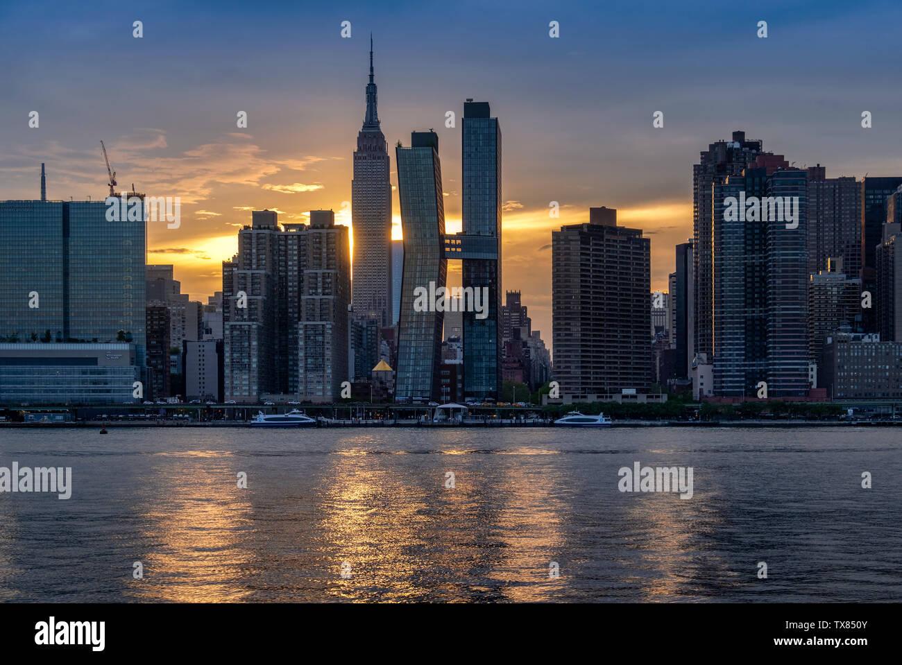 L'horizon de Manhattan et l'Empire State Building à travers l'East River au coucher du soleil, Manhattan, New York, USA Banque D'Images