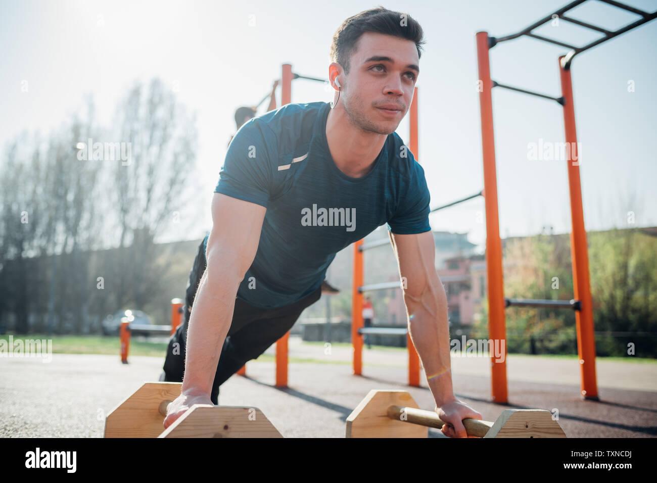 La gymnastique au sport en plein air, jeune homme faire poussez se lève sur l'équipement d'exercice Banque D'Images