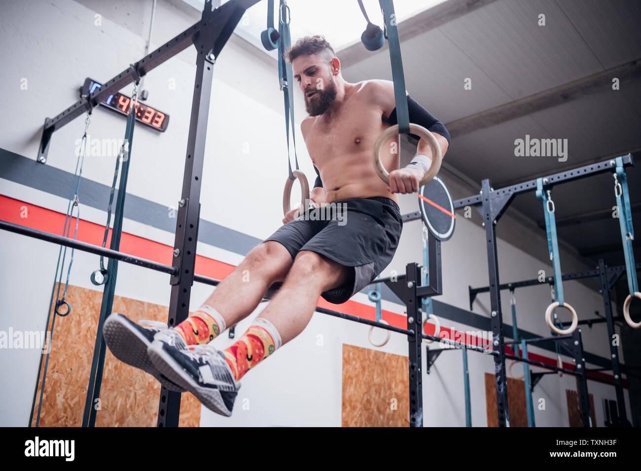 Jeune Homme En Equilibre Sur Les Anneaux De Gymnastique En Salle