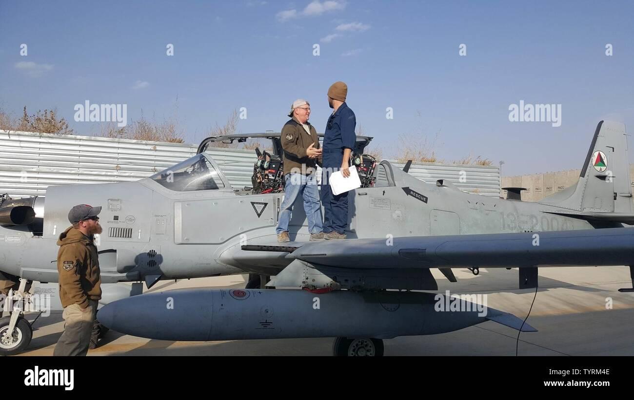 Un entrepreneur en entretien, serre la main avec un Afghan Air Force responsable d'aéronefs sur l'aile d'un A-29 Super Tucano à Hamid Karzaï, l'aéroport international de Kaboul, Afghanistan, le 23 novembre 2016. Les mainteneurs AAF a récemment effectué les 600 premières heures d'une inspection de l'avion A-29. Les responsables ont été en mesure de terminer l'inspection de trois semaines avec un minimum d'aide de la part des entrepreneurs. Banque D'Images