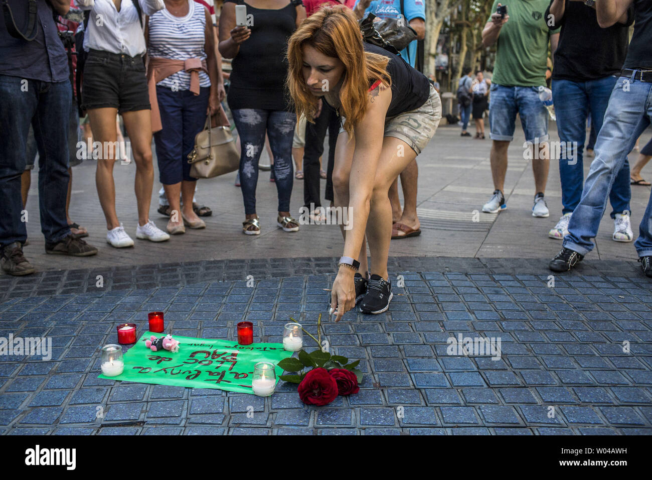 Une femme met des fleurs sur la Rambla pour les victimes de l'attaque de Barcelone le 18 août 2017, un jour après un van dans la foule, tuant 14 personnes et blessant plus de 100 sur la Rambla de Barcelone. Les conducteurs ont labouré le 17 août 2017. photo par Angel Garcia/ UPI Banque D'Images