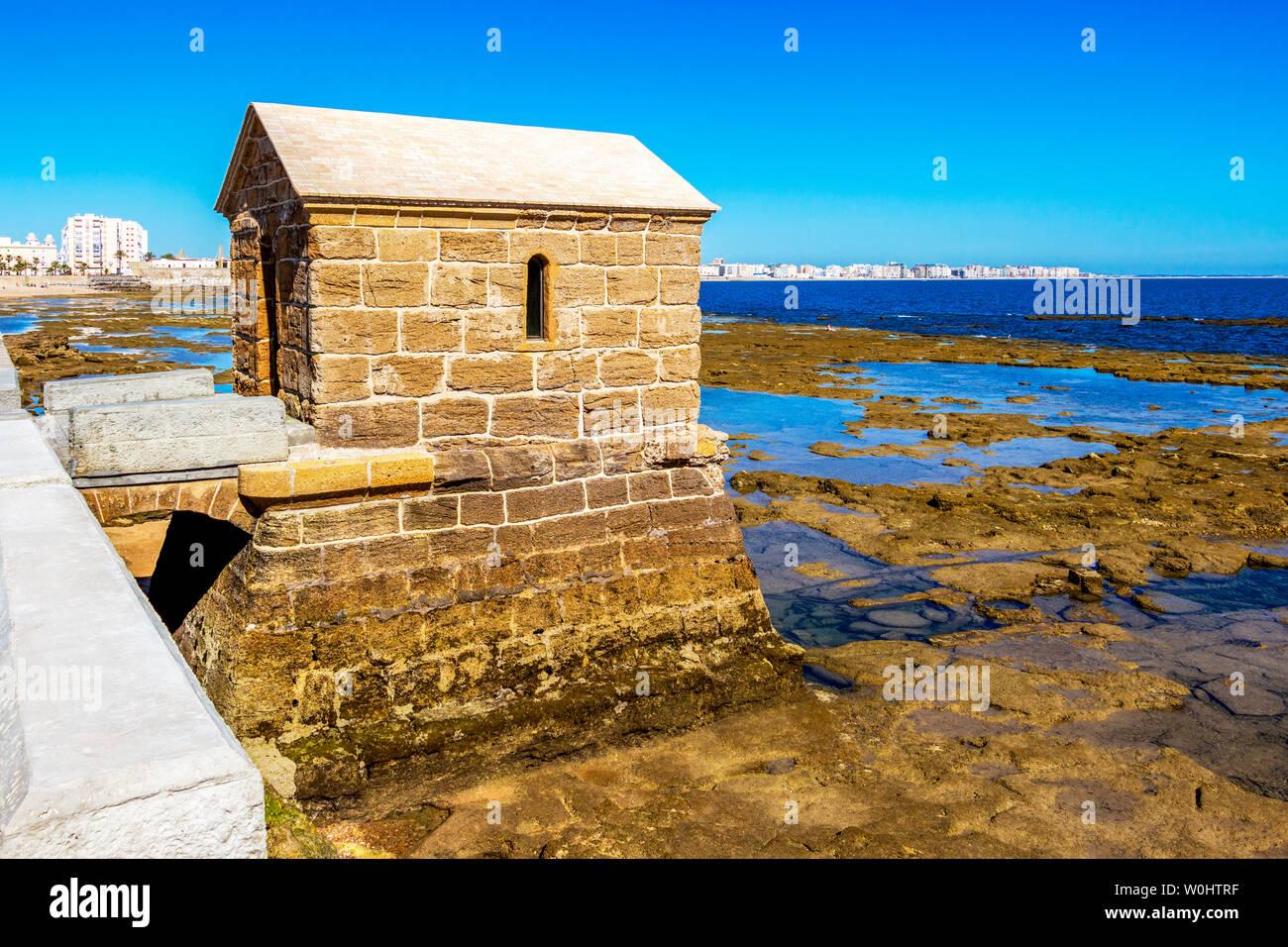 Mareografo mareometer marégraphe, ou des capacités au château de San Sebastian causeway avec littoral, vue de Cadix dans l'arrière-plan, en Andalousie, Espagne Banque D'Images
