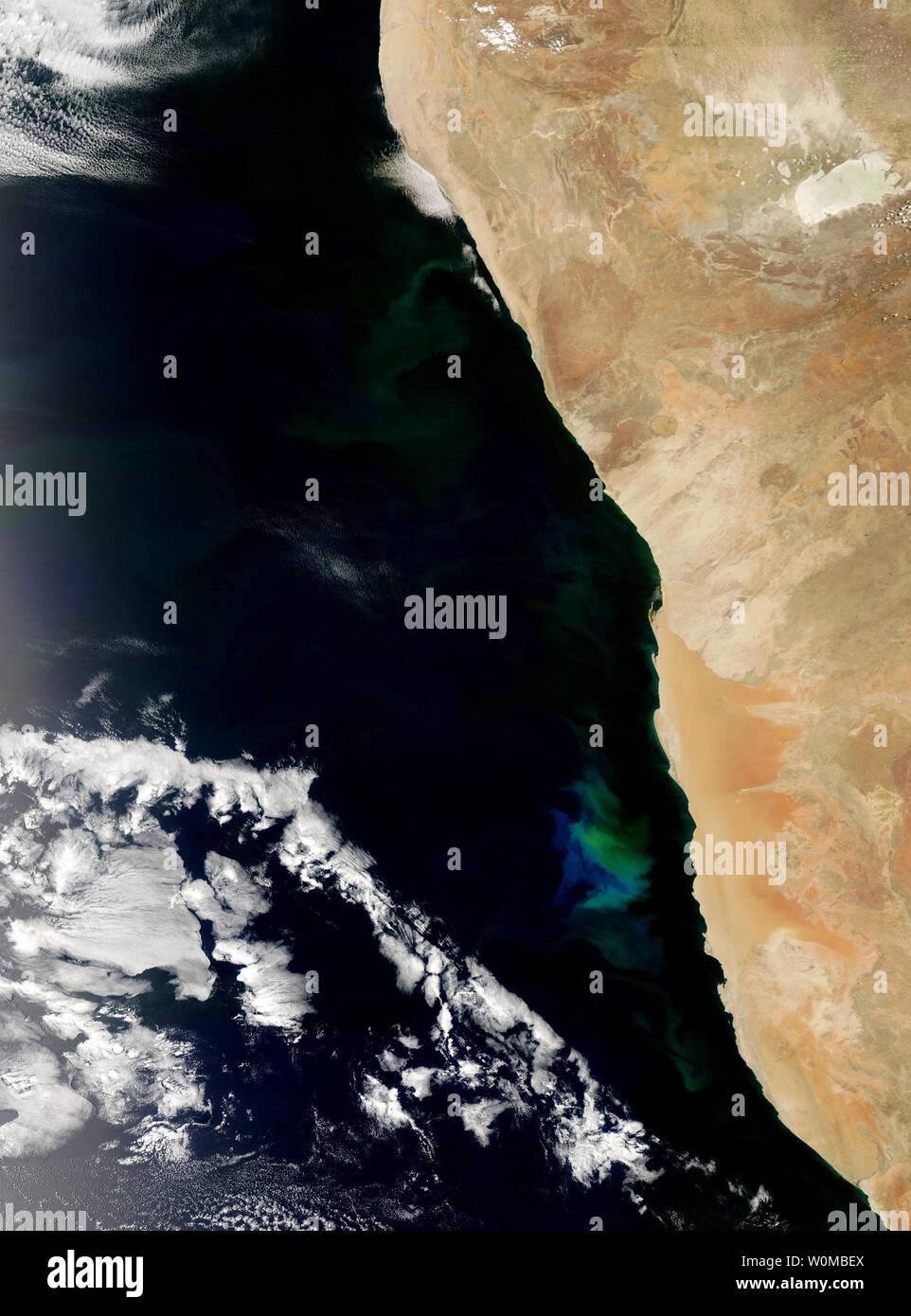 Feu vert et bleu les eaux au large de la Namibie au début de novembre 2007 comme une prolifération du phytoplancton a grandi et a disparu dans l'océan Atlantique. La floraison s'étend du nord au sud le long des centaines de kilomètres, même si elle est plus lumineuse dans le centre de cette image. Ces algues sont communes dans les eaux côtières au large du sud-ouest de l'Afrique où le froid, les courants riches en éléments nutritifs du balayage de l'Antarctique et interagir avec la plate-forme côtière. (Photo d'UPI/NASA) Banque D'Images