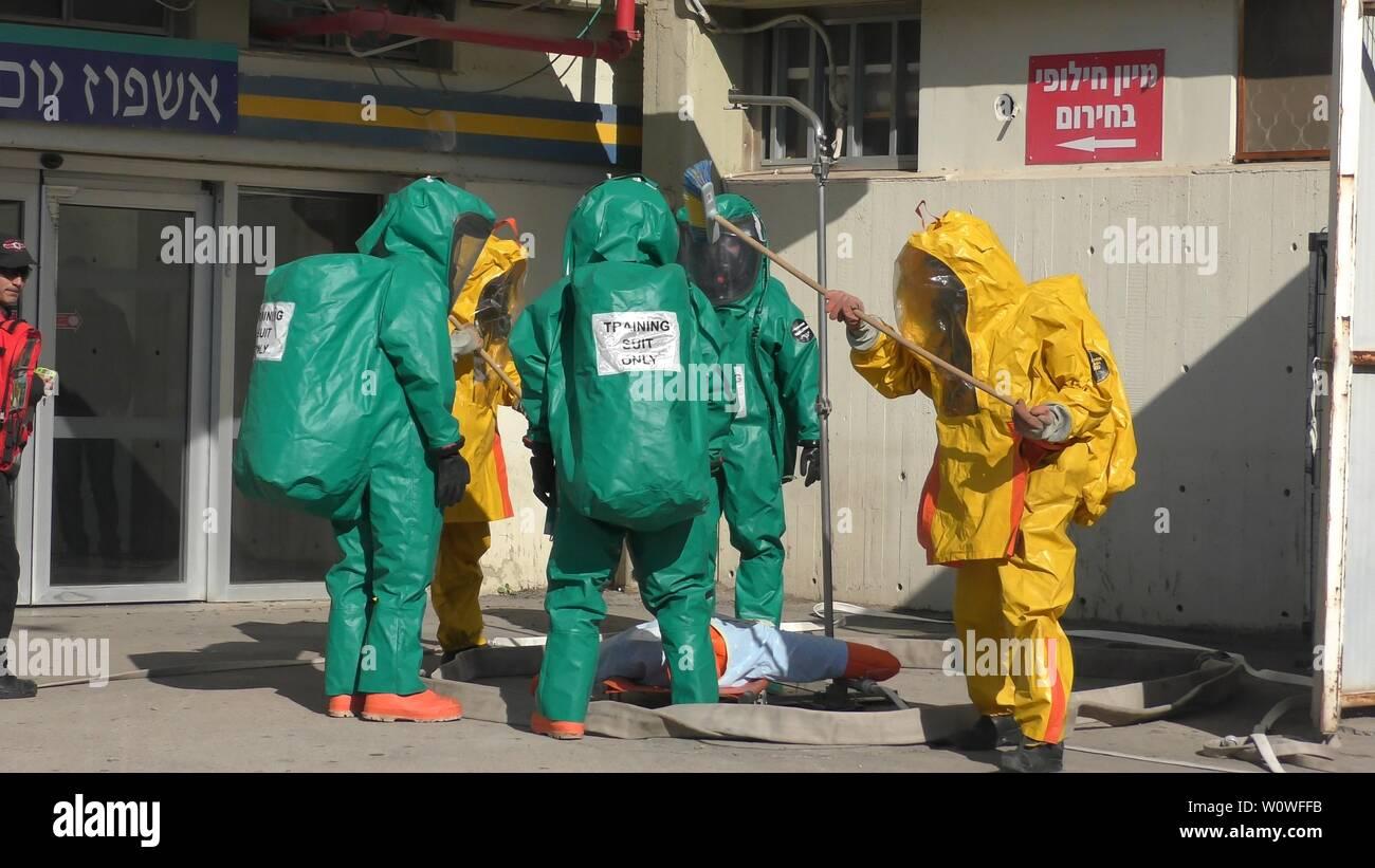 Les pompiers de protection nettoyage suites vinaigrette de fuir les victimes des gaz médicaux toxiques à l'hôpital Haemek au cours de l'exercice. Afula, Israël, le 30 janvier, 2017 Banque D'Images