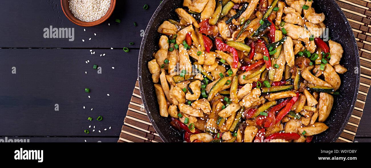 Faire revenir le poulet, les courgettes, poivrons et l'oignon vert. Vue d'en haut. Bannière. La cuisine asiatique Banque D'Images