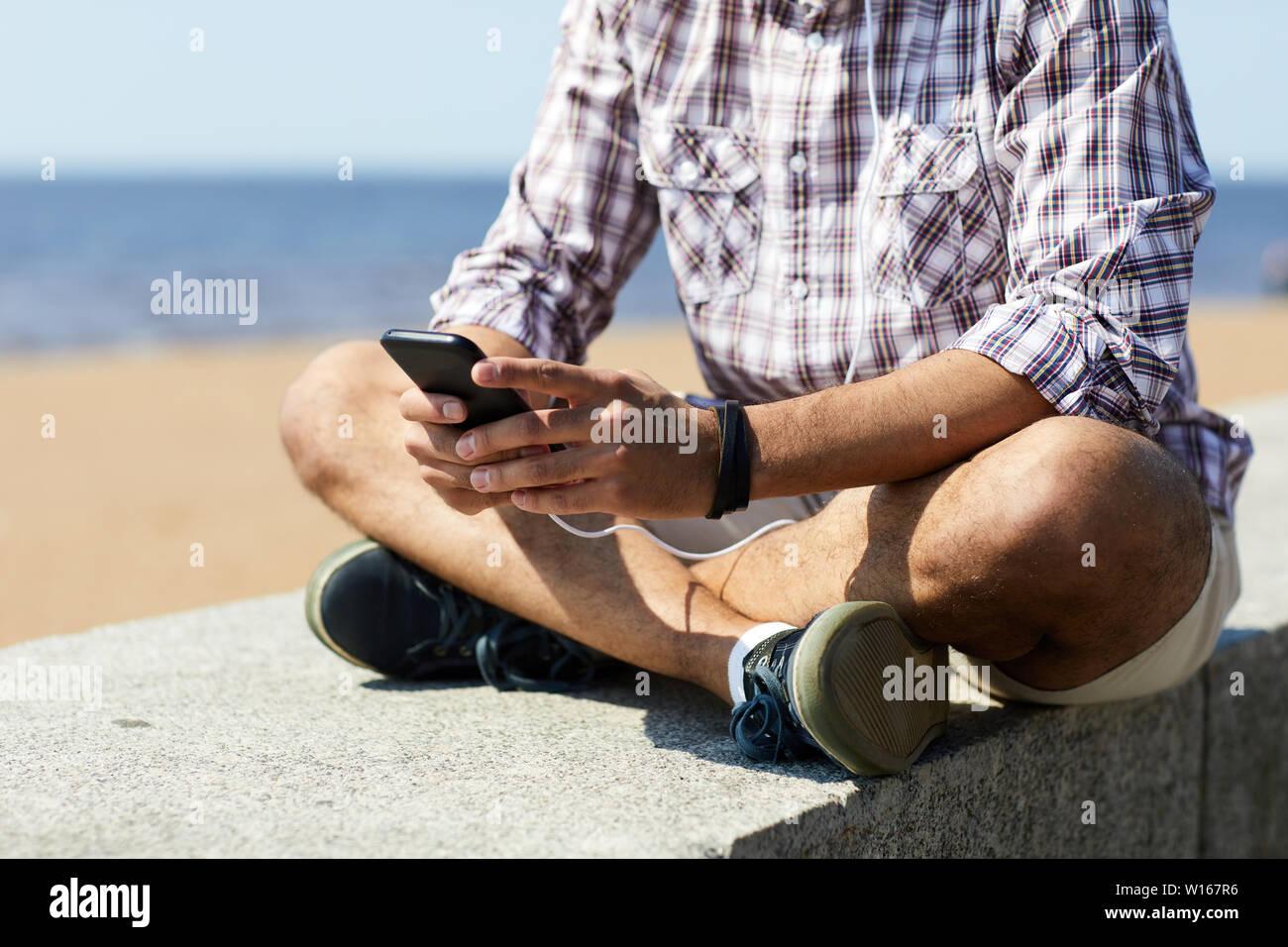 Mid section portrait of young man using smartphone contemporain assis sur des blocs de béton par mer, copy space Banque D'Images