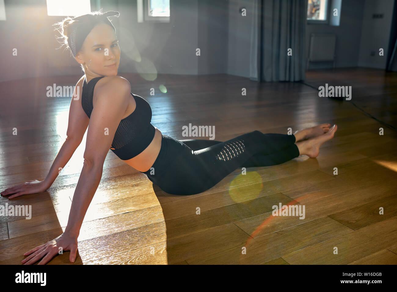 Matin girl doing yoga des exercices d'étirement dans la chambre pour le Pilates. Belle Lumière, de photos aériennes, d'un mode de vie sain, les hormones du corps et âme Banque D'Images