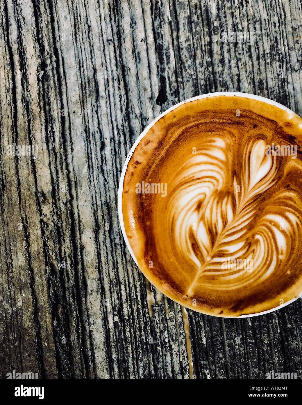 Tasse de café latte sur table en bois sombre, belle latte art Banque D'Images