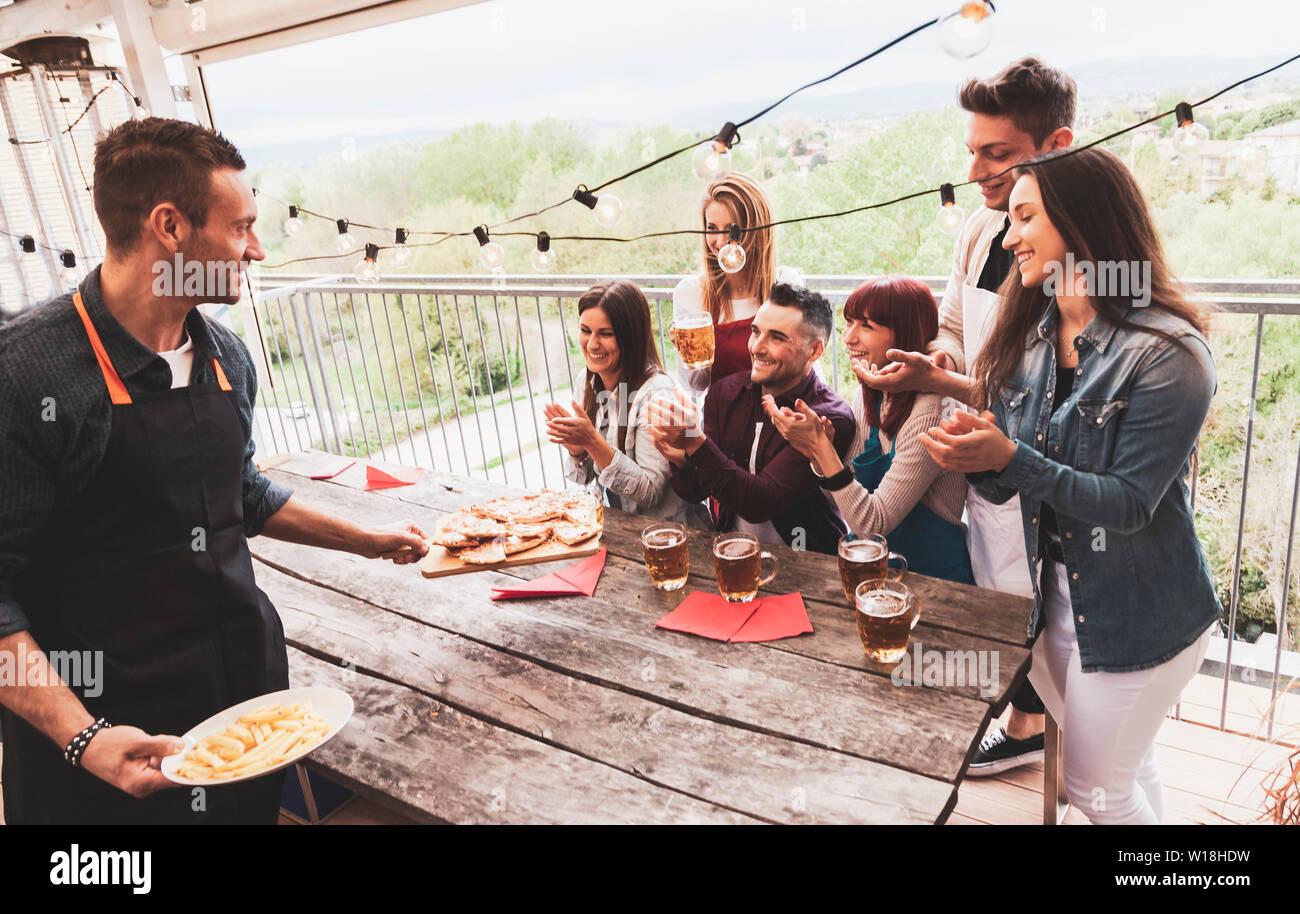 Groupe d'amis heureux de boire une bière et manger une pizza à la brasserie bar restaurant. concept avec des jeunes ayant un véritable plaisir Banque D'Images