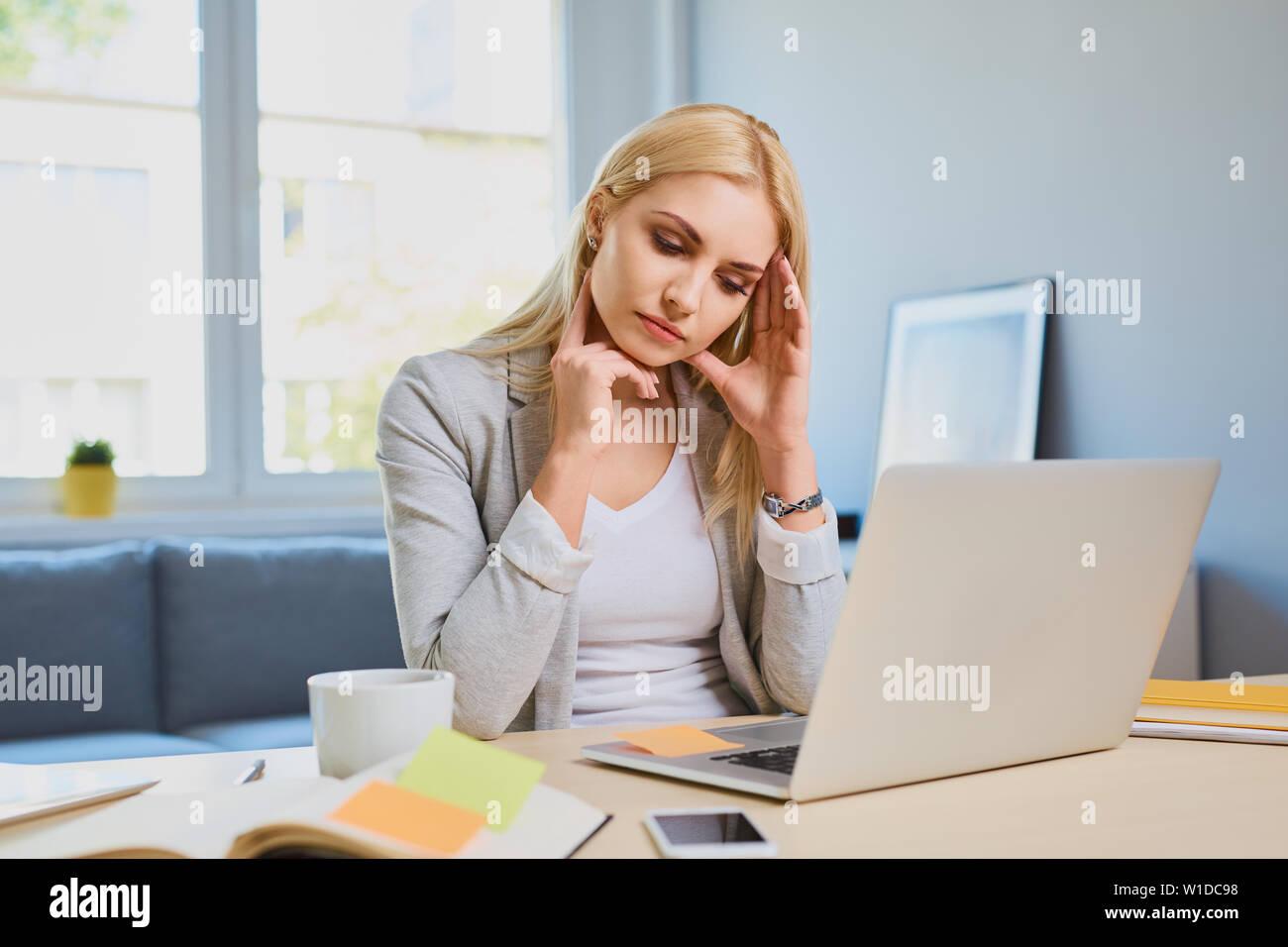 Jeune femme souffrant de maux de tête tout en travaillant en home office Banque D'Images