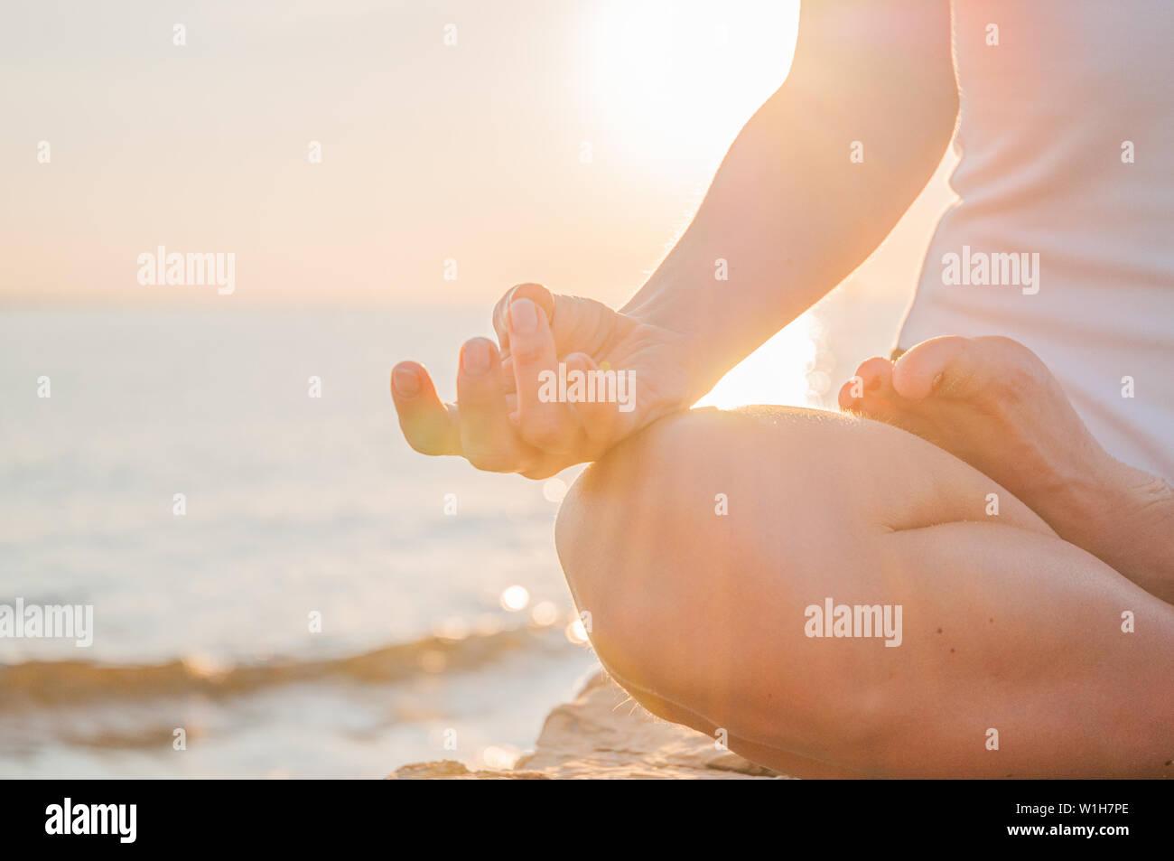 La femme est en méditant sur la calme plage au coucher du soleil. Femme est la pratique du yoga assis en Lotus posent au lever du soleil. Silhouette de femme méditant sur la beac Banque D'Images