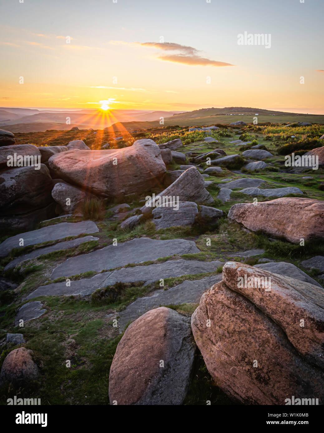 Scène Coucher du soleil dans les régions rurales de Peak District, Derbyshire, UK.des pierres en haut de la colline éclairée par horizon soleil derrière.Ethereal soir paysage.ima Paysage Banque D'Images