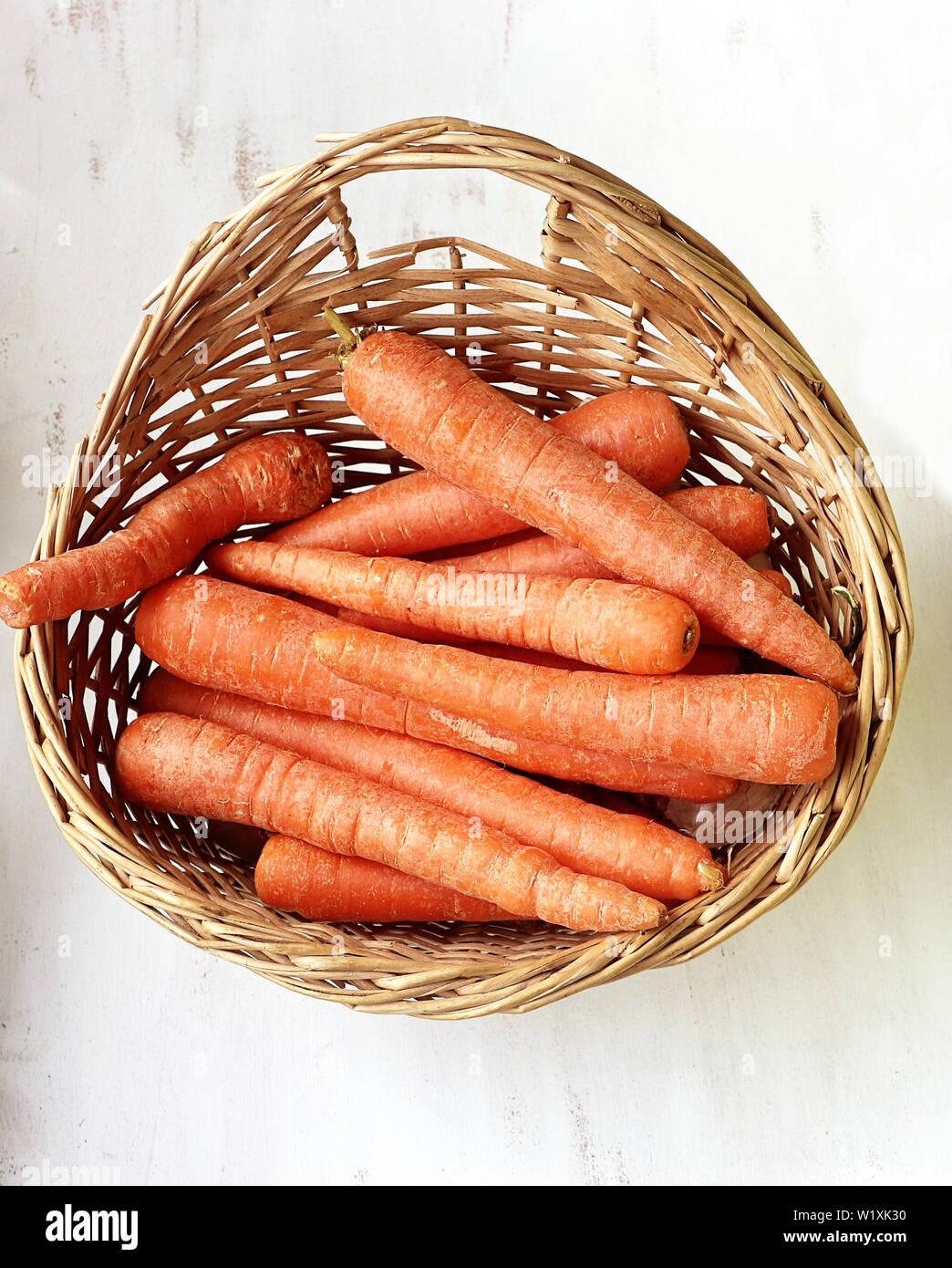 Les carottes avec des couleurs vives dans un panier sur la table de cuisine Banque D'Images
