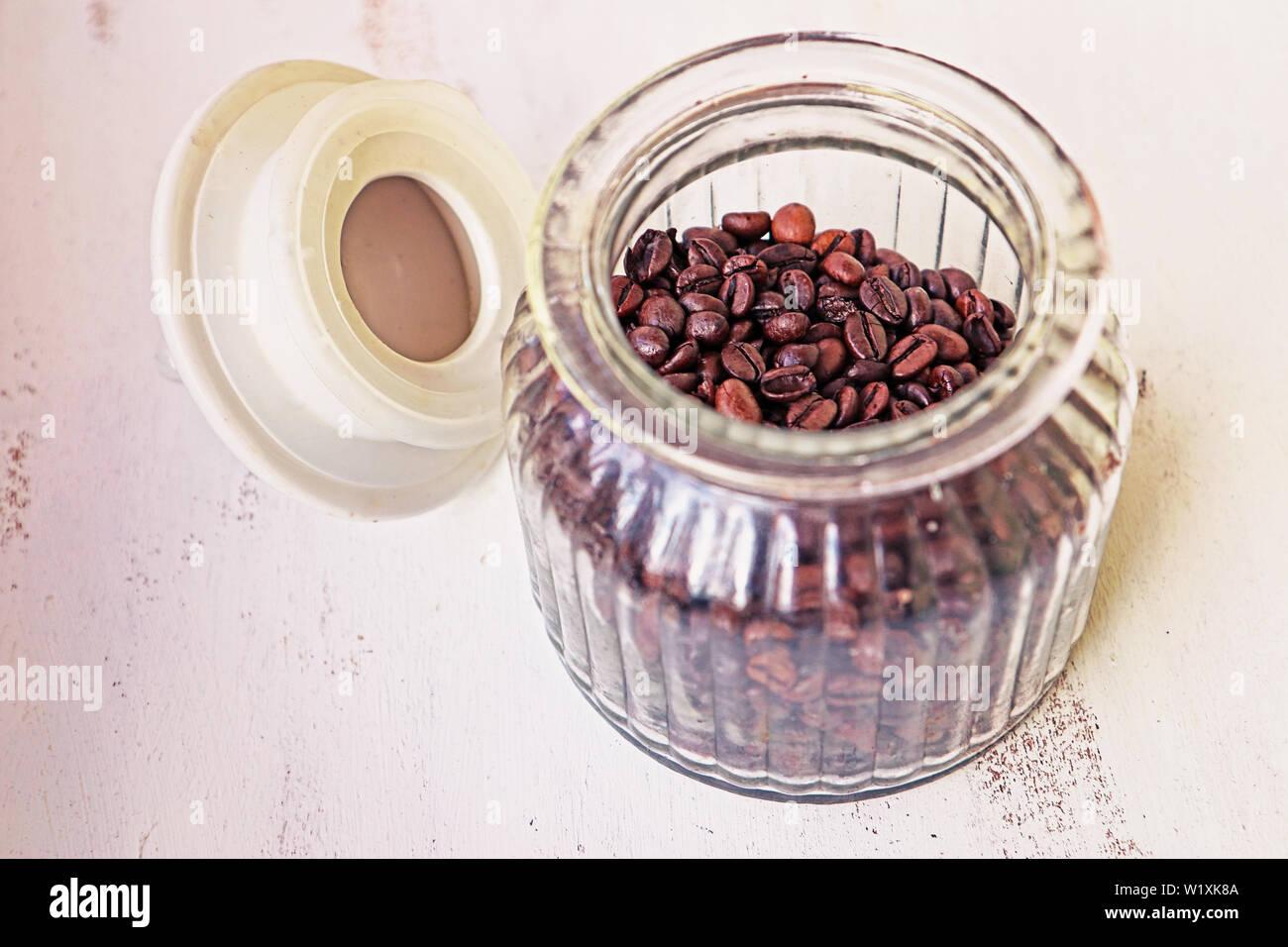 Les grains de café torréfié en vase en verre sur la table de cuisine Banque D'Images