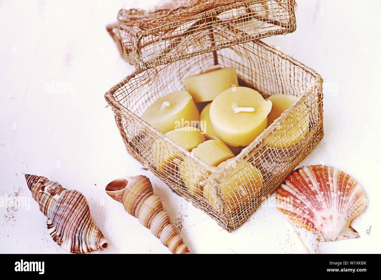 Still Life: chandelles en cire d'un treillis métallique en or fort de coquillages sur une table en bois blanc, vue du dessus Banque D'Images