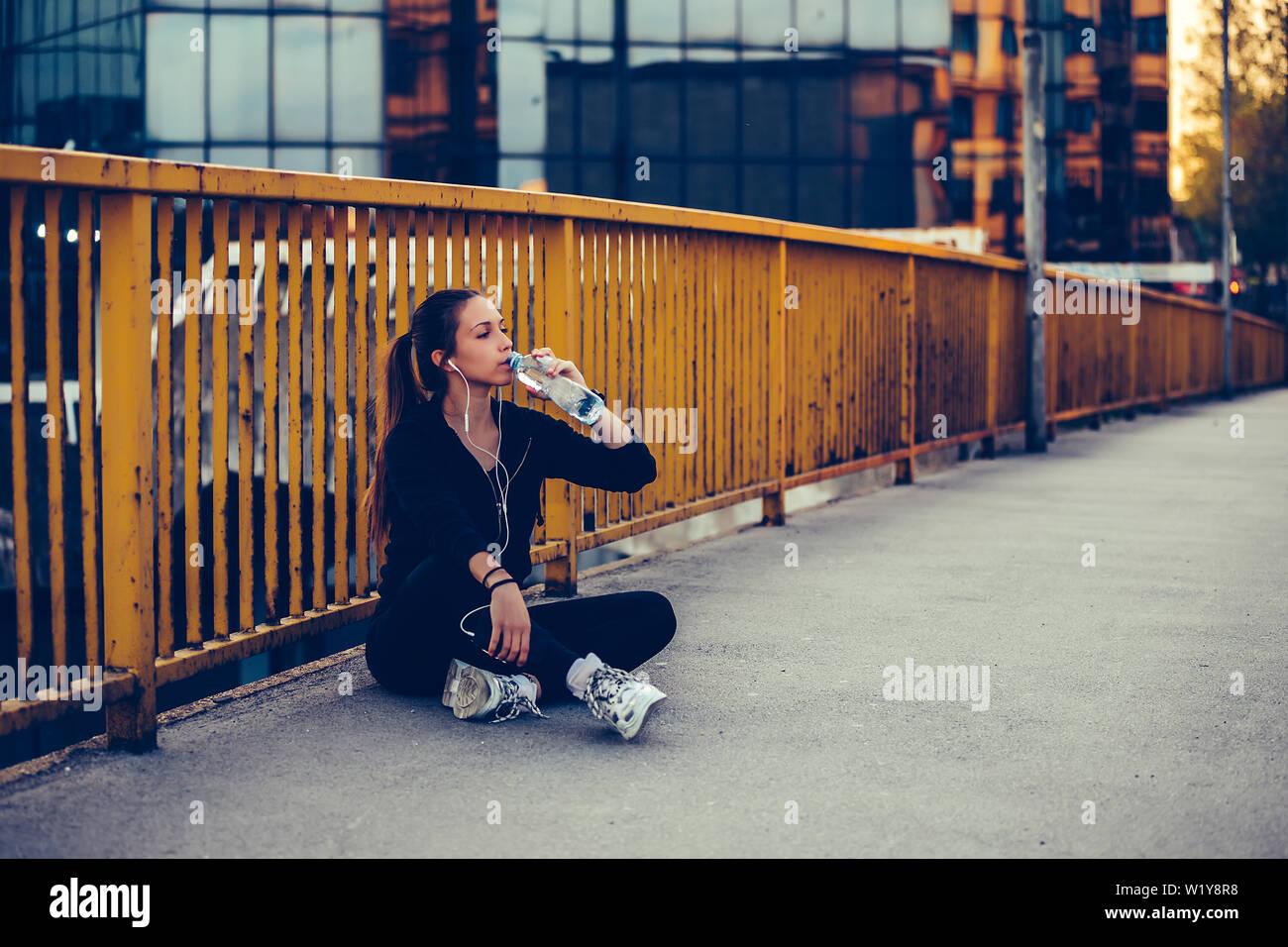 Coureuse assis sur le pont et l'eau potable à partir d'une bouteille. Femme de remise en forme en faisant une pause après l'exécution de l'entraînement. Banque D'Images