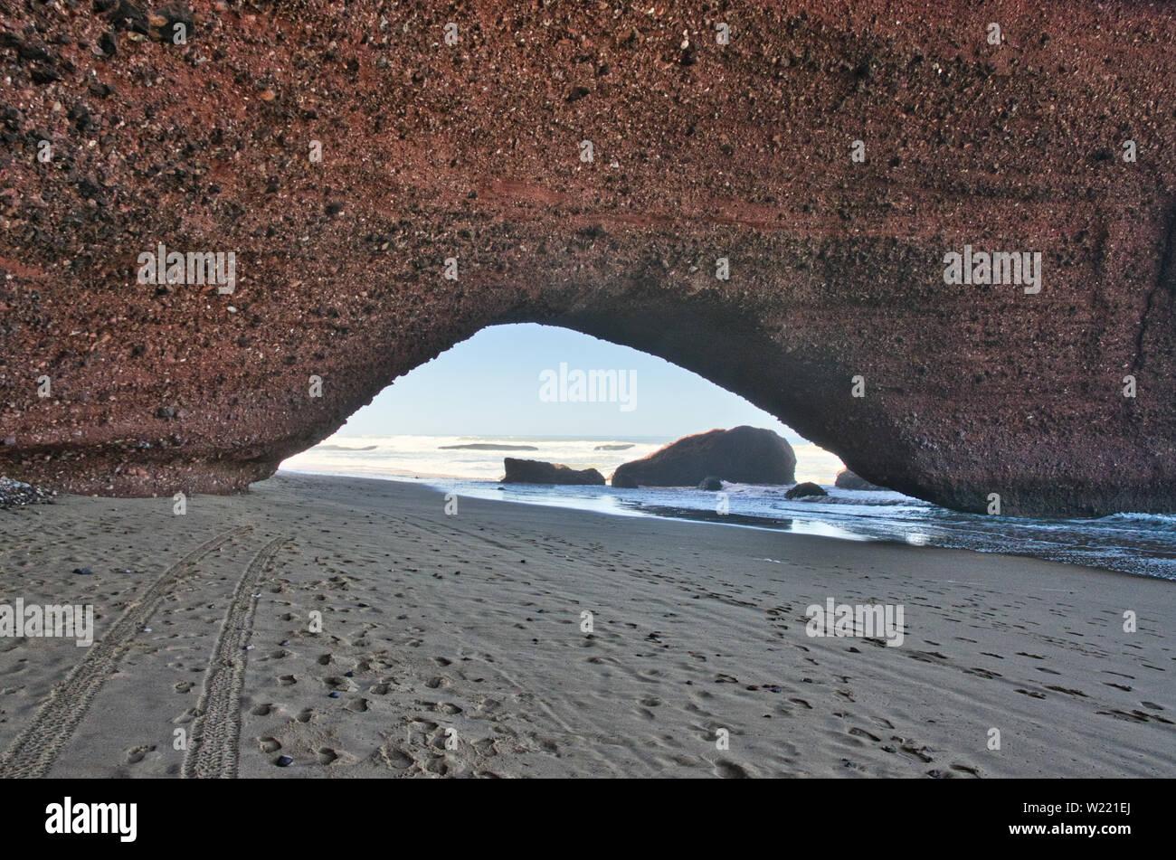 Red Rock formation avec arch sur la plage, plage Sidi Ifni, Maroc, Afrique Banque D'Images