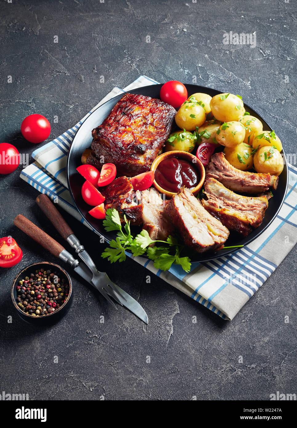 Côtes de porc grillées recouvertes de sauce barbecue servi avec des tomates et de l'eau chaude les pommes de terre servies sur un plateau noir sur une table, vue verticale Banque D'Images