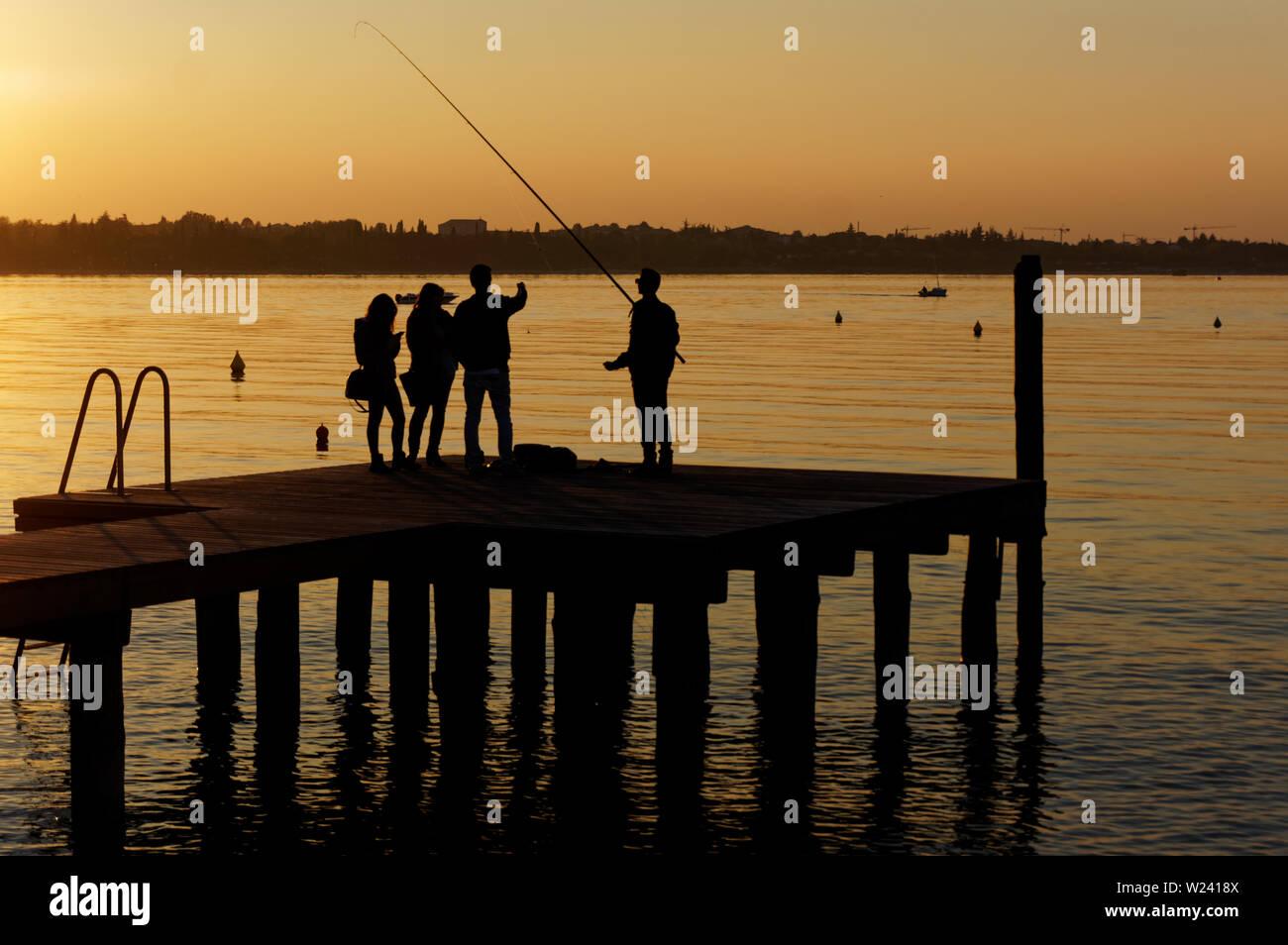 Groupe de jeunes gens et de parler de pêche sur la jetée, méconnaissable personnes Banque D'Images