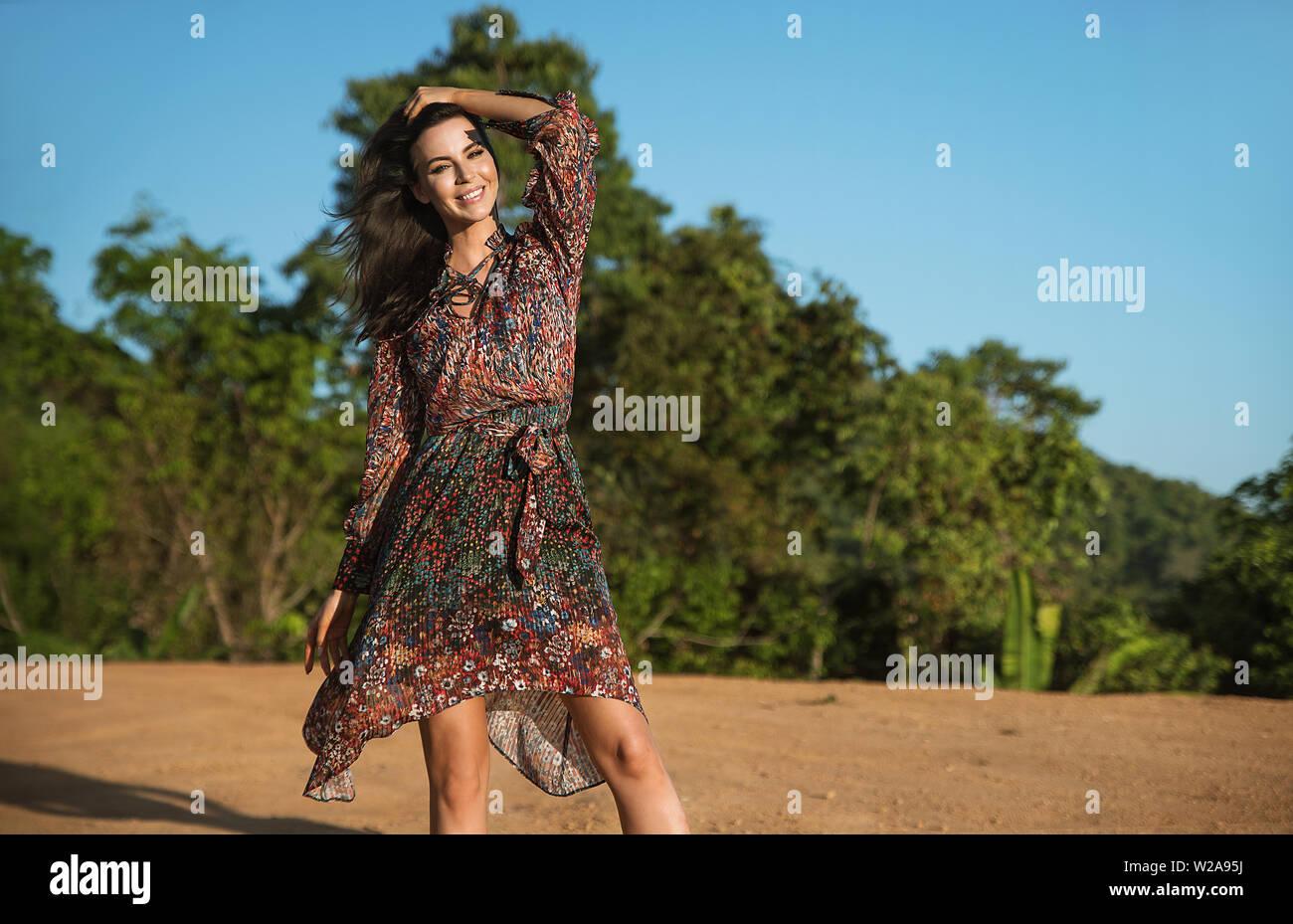 Portrait d'une jolie brunette posing délicate contre les bois tropicaux Banque D'Images