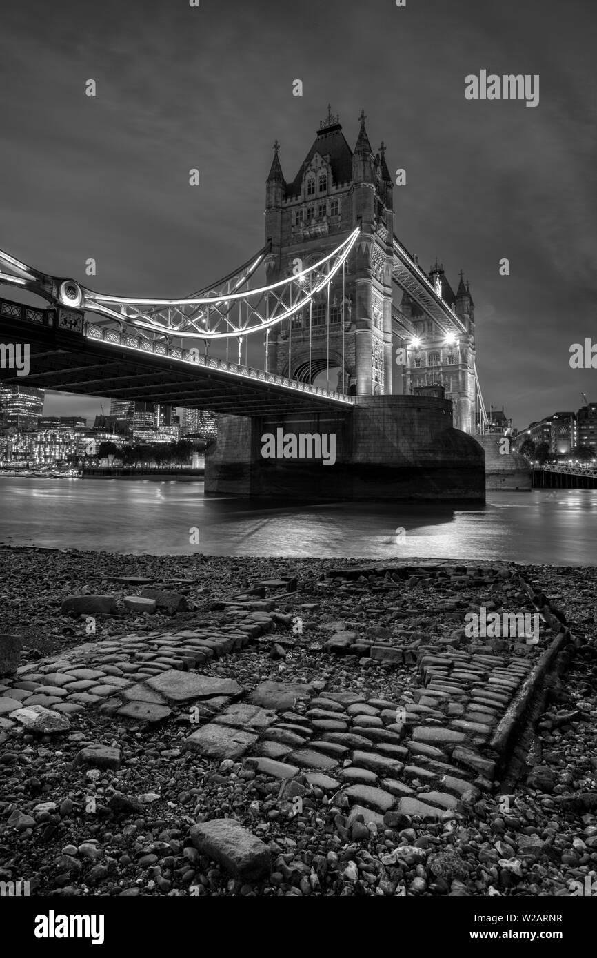 Tower Bridge, Londres, l'emblématique pont qui enjambe la Tamise, photographié de nuit, image en noir et blanc Banque D'Images