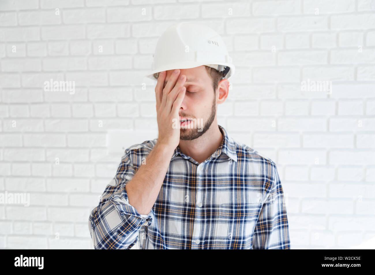 Un col bleu portant un casque est couvrant son visage avec sa main. Banque D'Images