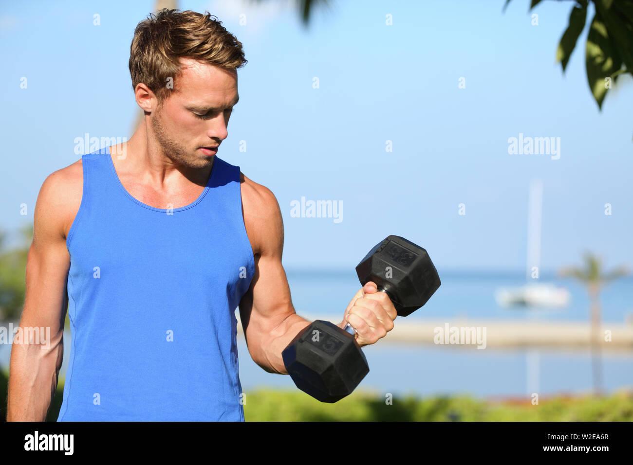 Formation de bicep - poids à l'extérieur de l'homme remise en forme lifting du bras faisant haltères biceps. Modèle sport masculin exerçant à l'extérieur dans le cadre de vie sain. Photo Stock