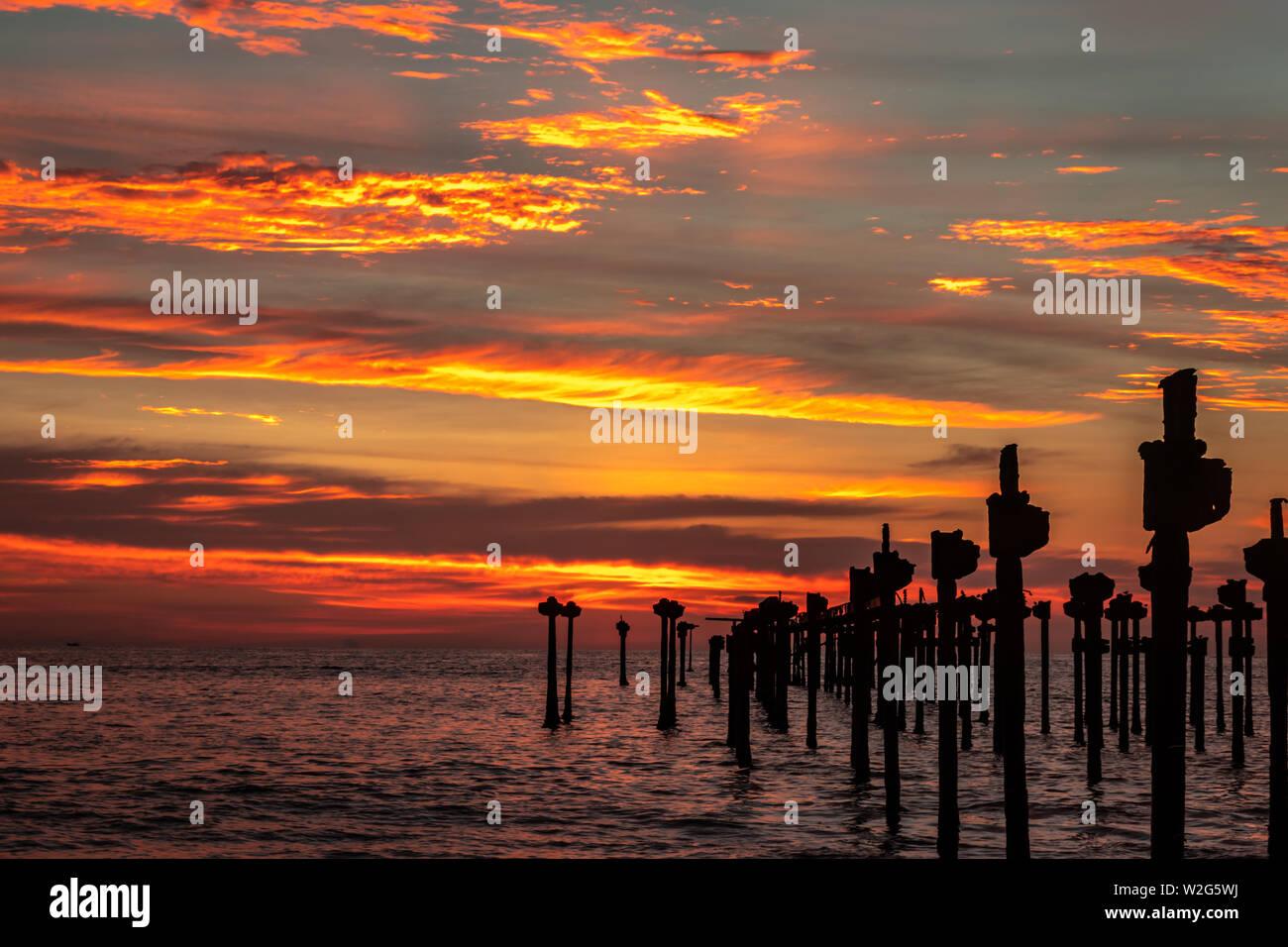Nuages orange sur l'horizon de mer avec des poteaux de fer vers le soleil Banque D'Images