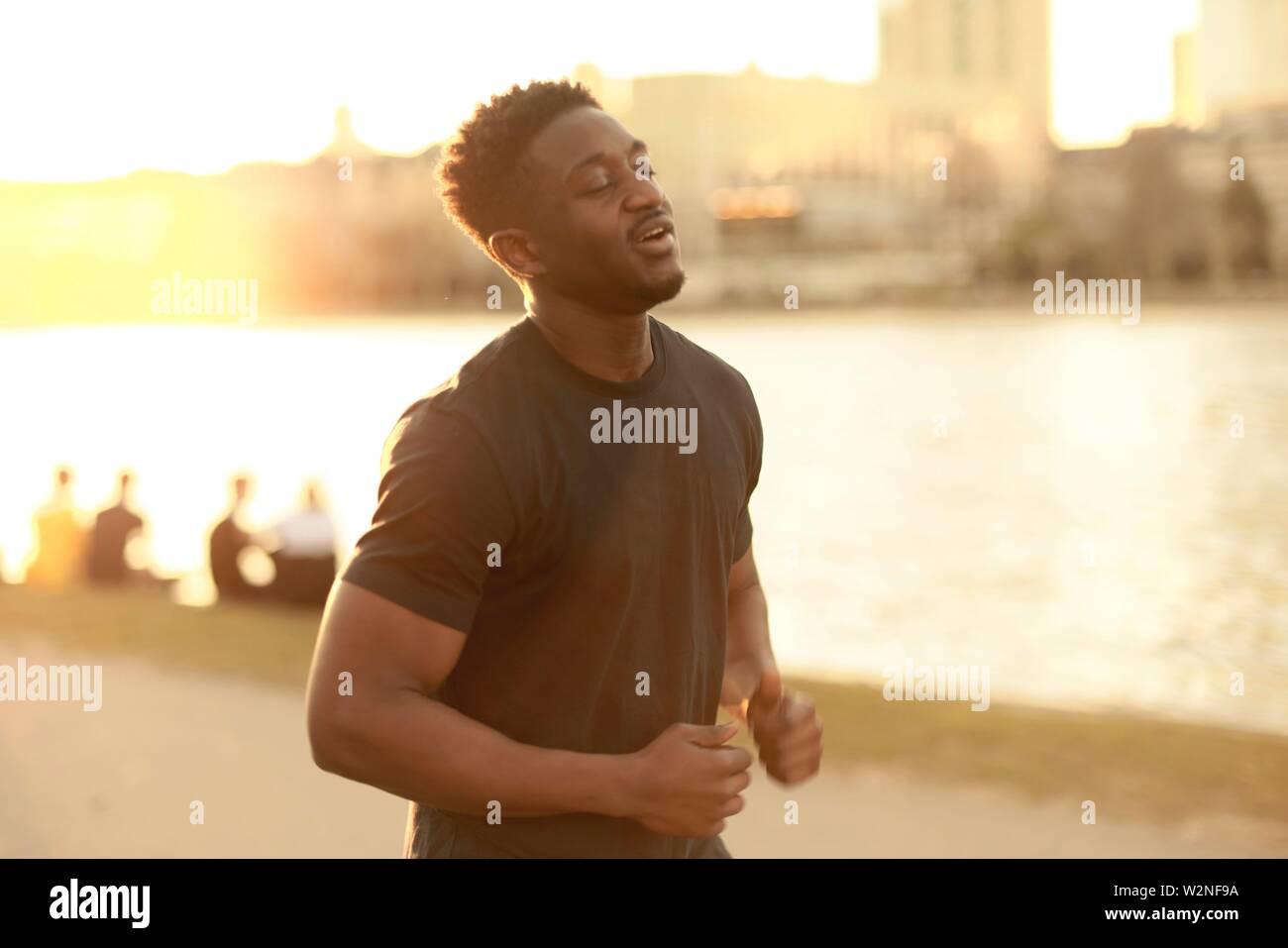 African man jogging à côté de la rivière Main, à Francfort, Allemagne. Banque D'Images