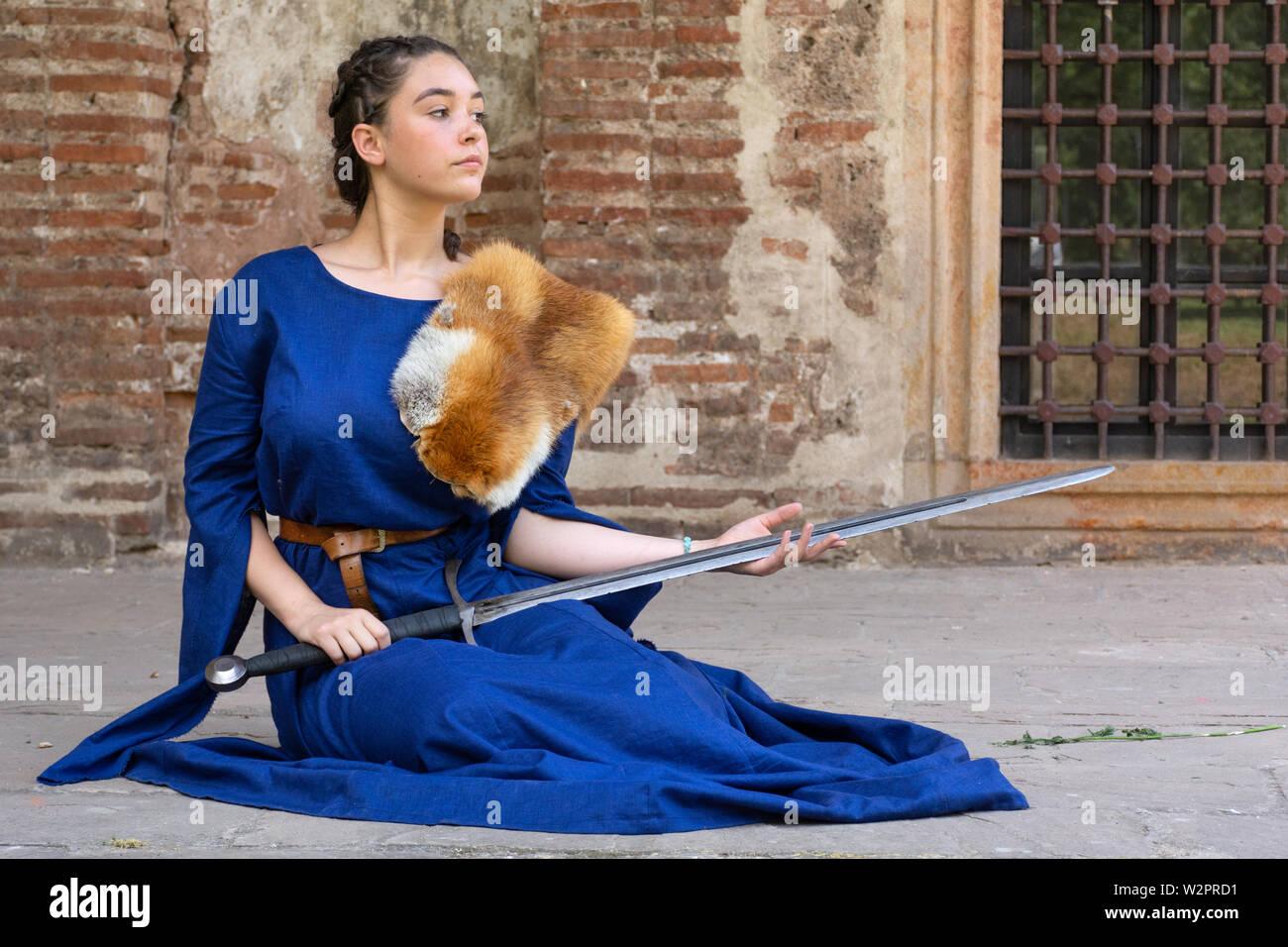 Nis, Serbie - 15 juin. 2019 dame médiévale dans une robe bleue avec fourrure de renard sur l'épaule est titulaire d'une épée dans ses mains et se repose sur le plancher Banque D'Images