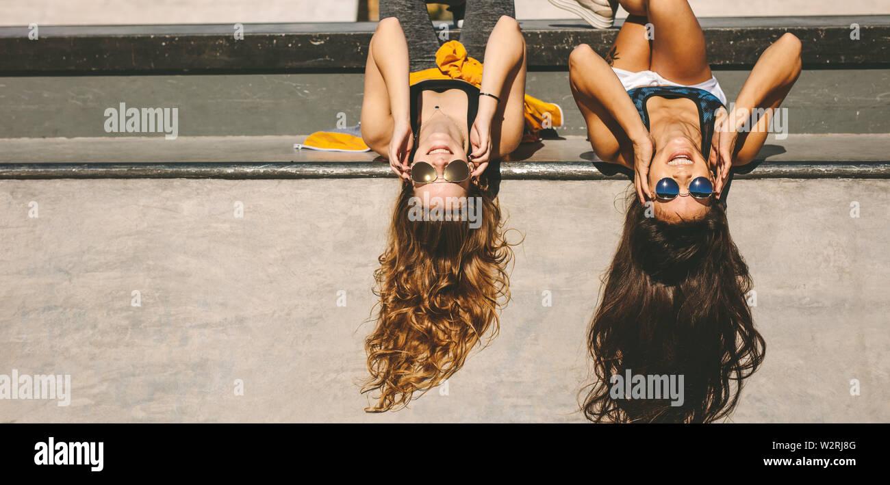Deux filles élégant couché au skate park avec des lunettes. Female friends having fun at skate parc un jour d'été. Banque D'Images