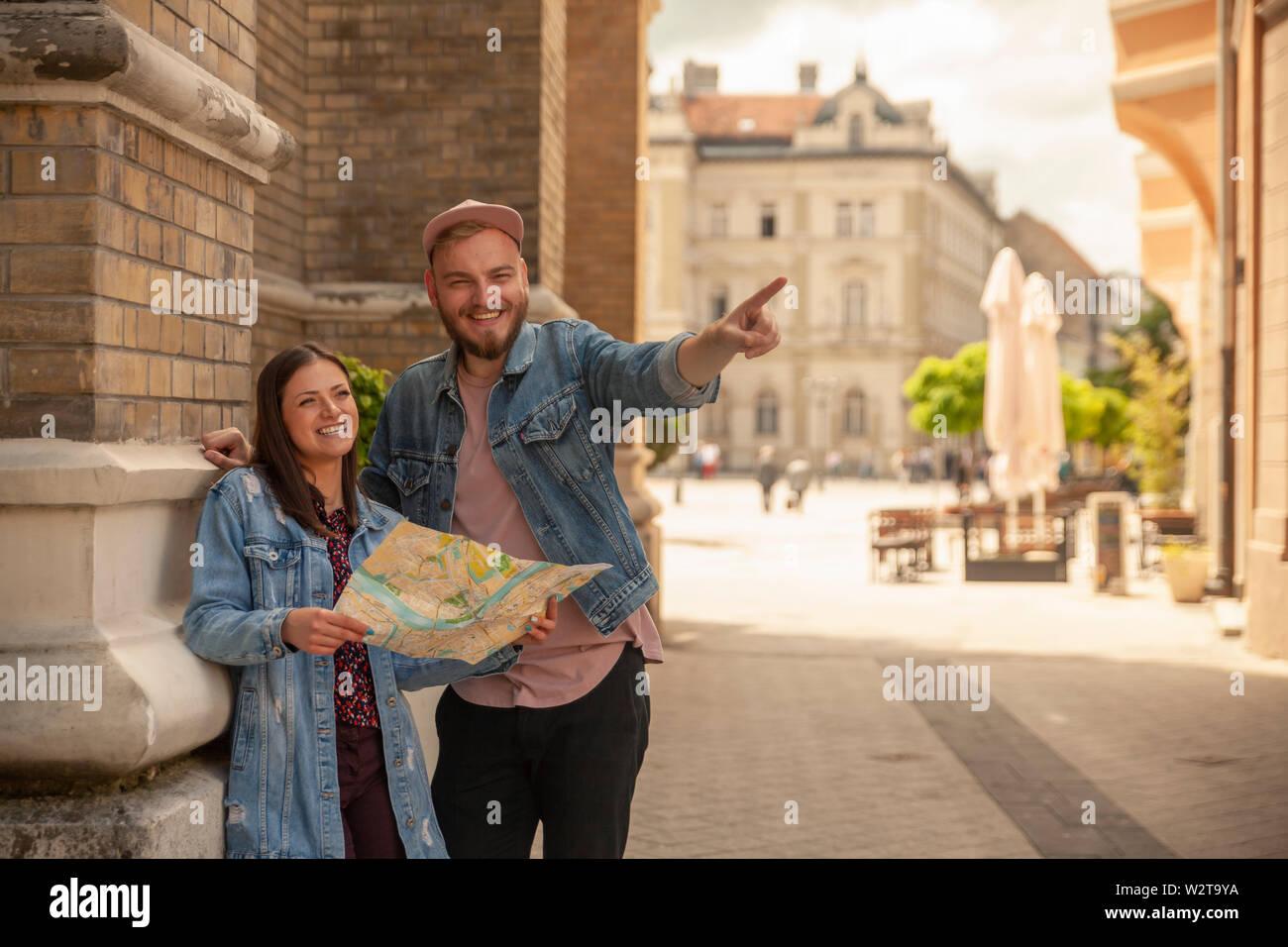 Deux amis, ou en couple, à la recherche d'un plan de la ville tandis que l'homme est un doigt pointé. Location Novi Sad, Serbie. Banque D'Images