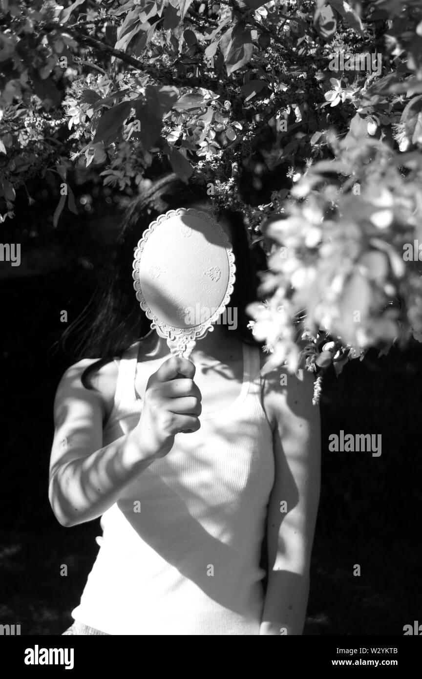Un auto-portrait avec un arbre en fleurs et un miroir cachant mon visage. Banque D'Images