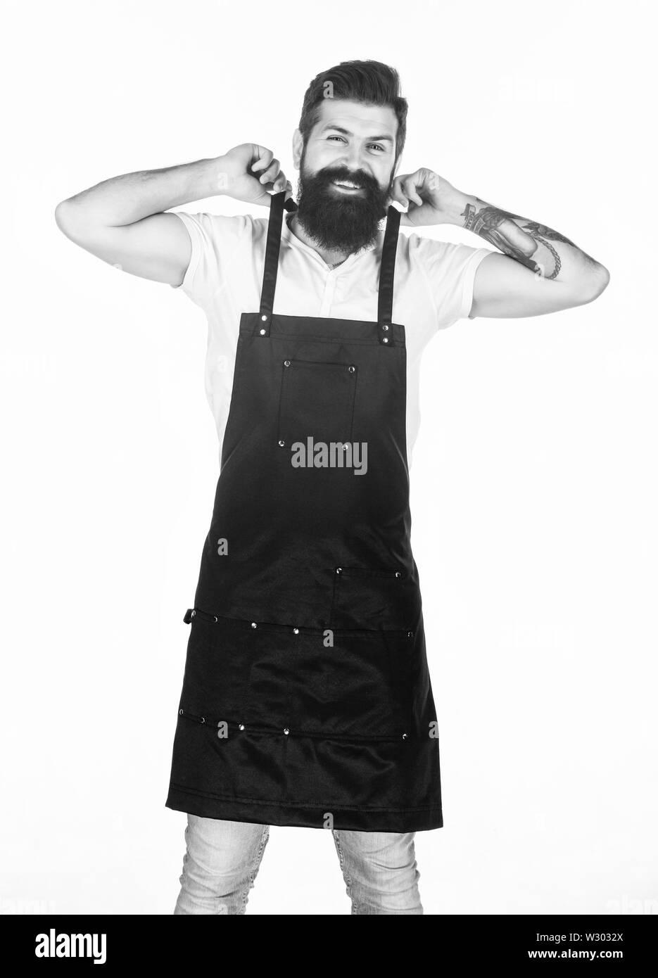 Suivant la même routine de travail. Hipster se préparer pour les jours à barbier ou de cuisine. Homme barbu portant un tablier de travail au quotidien. Activités courantes. Photo Stock