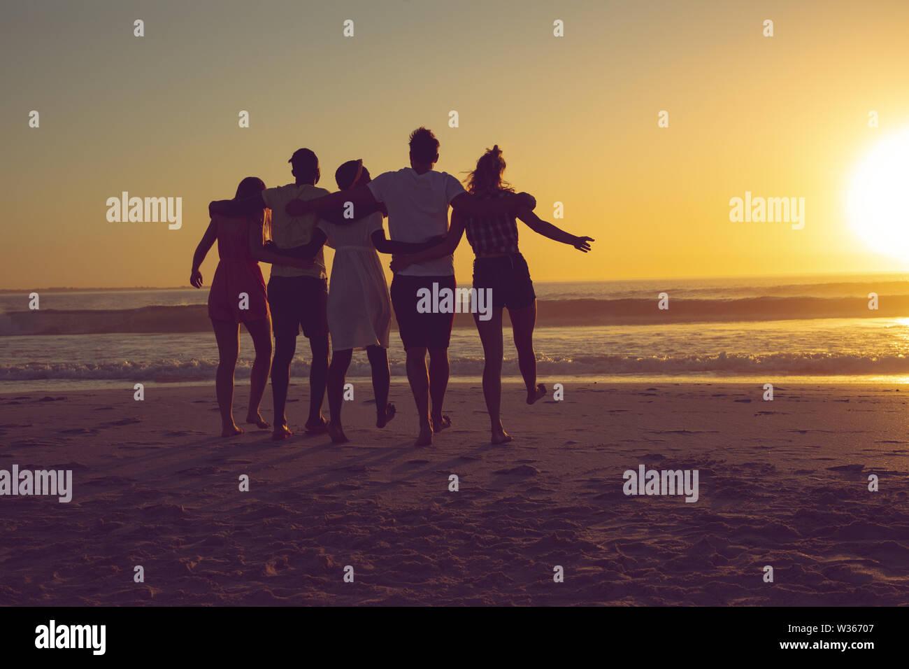 Amis avec bras autour de marcher vers la plage pendant le coucher du soleil Banque D'Images