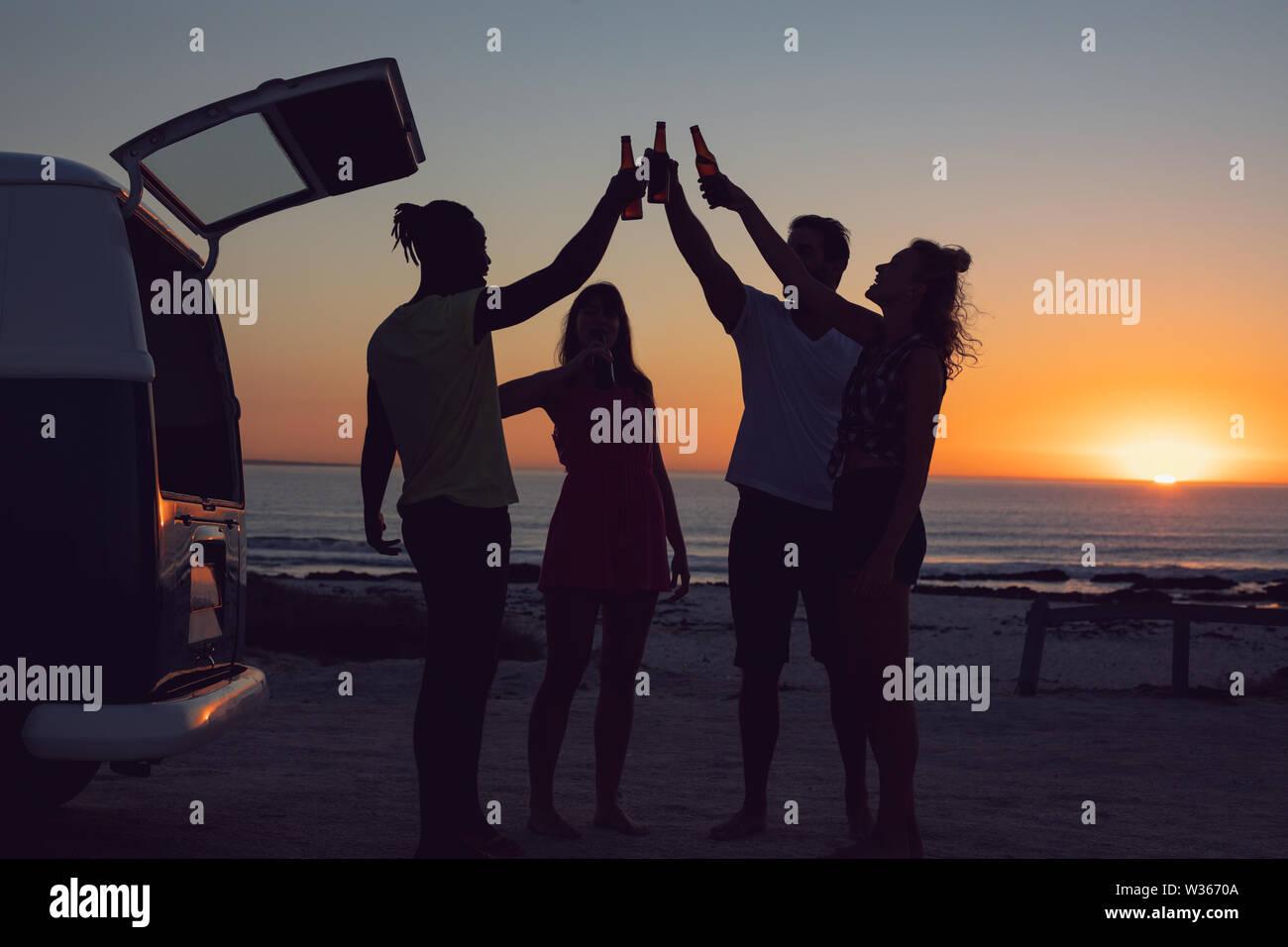 Friends toasting beer bottles près de camping-van pendant le coucher du soleil Banque D'Images