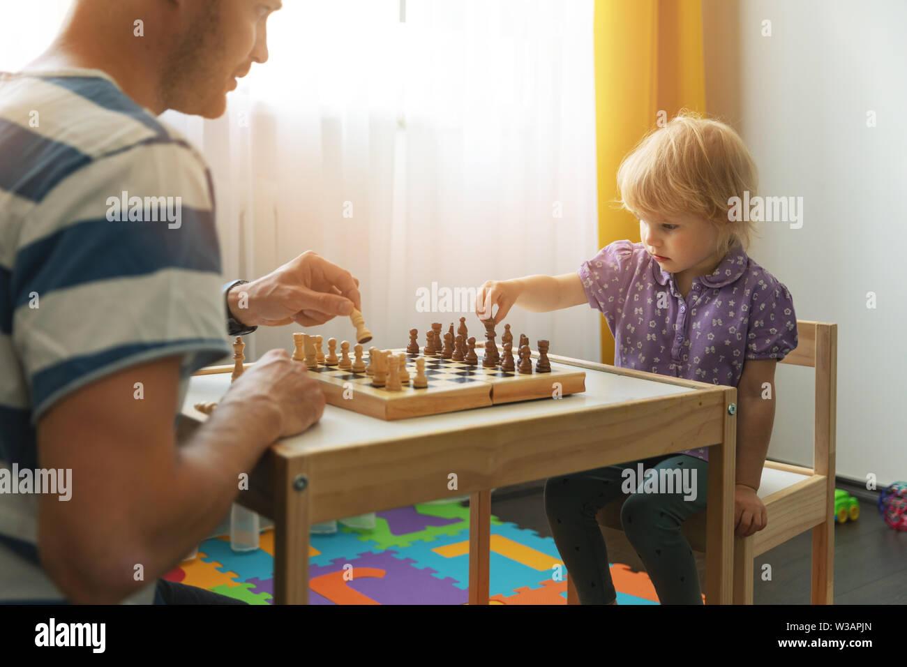 Cerveau jeux - père apprend à jouer aux échecs pour son enfant à la maison Banque D'Images