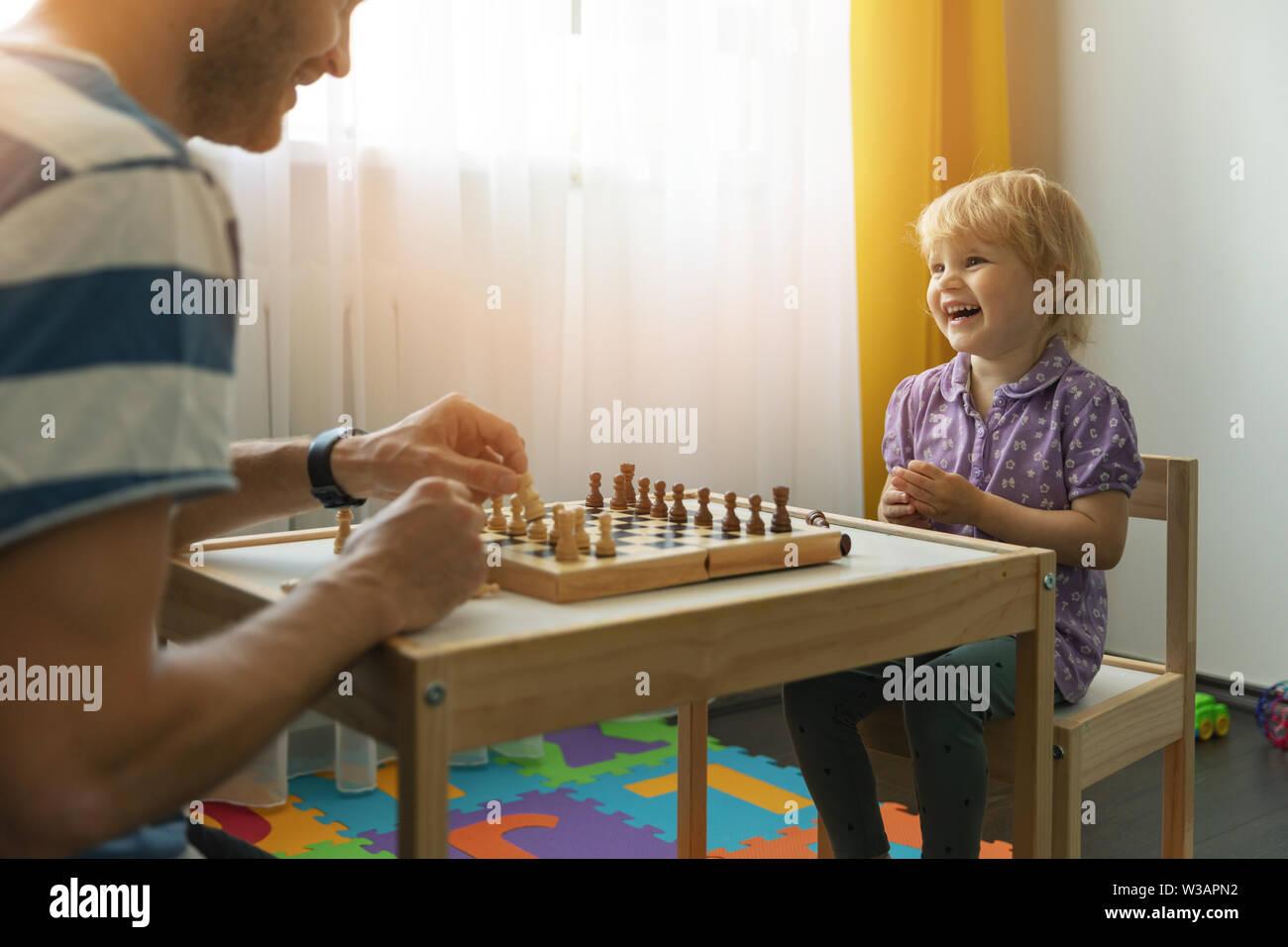 Père et fille de s'amuser ensemble apprendre à jouer aux échecs à la maison Banque D'Images
