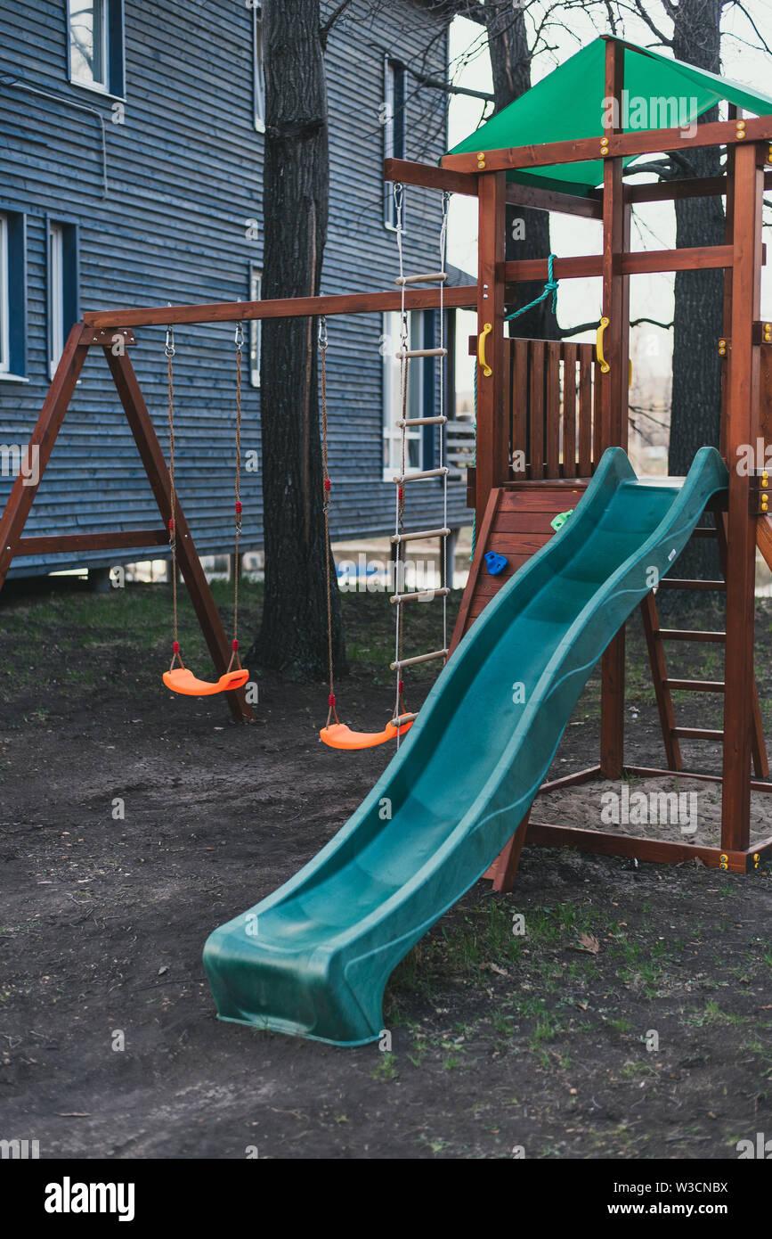 Faites glisser l'enfant plastique bleu sur un jeu en bois complexe. Aire de jeux pour enfants sans que personne. Banque D'Images