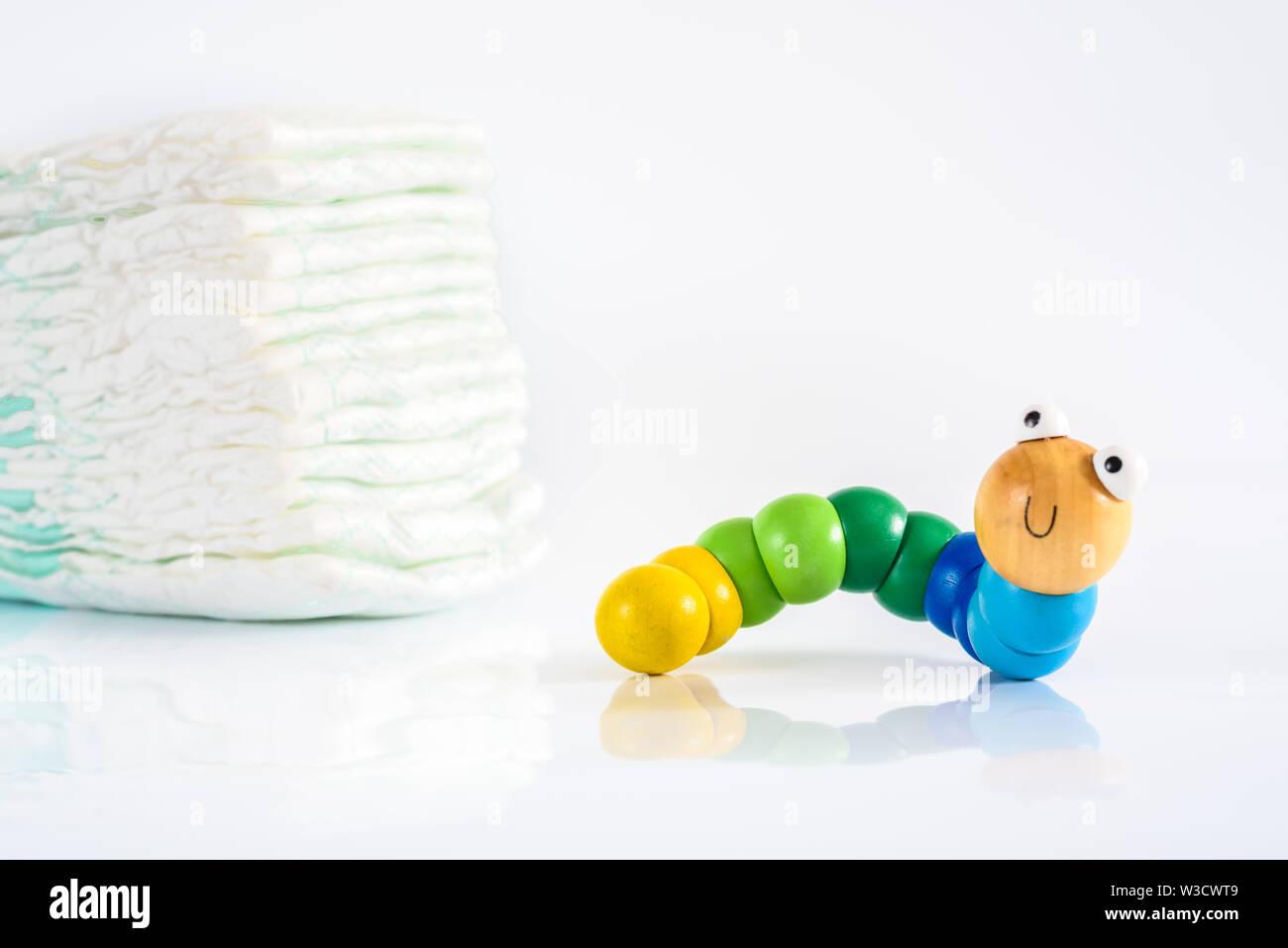 Toy ver avec sourire à côté d'une pile de couches, pour illustrer les concepts de la santé et de l'enfance maladies intestinales. Isolated on white Photo Stock