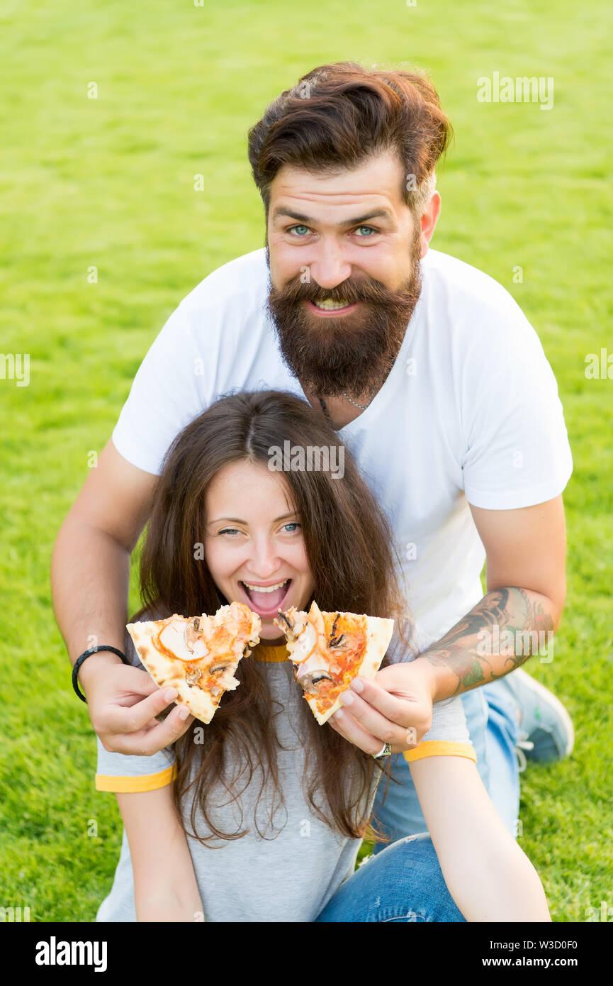 Funny time. été pique-nique sur l'herbe verte. Régime alimentaire. heureux couple eating pizza. Alimentation saine. couple in love dating. la faim. week-end en famille. restauration rapide. barbu hipster et jolie femme manger une pizza. Banque D'Images
