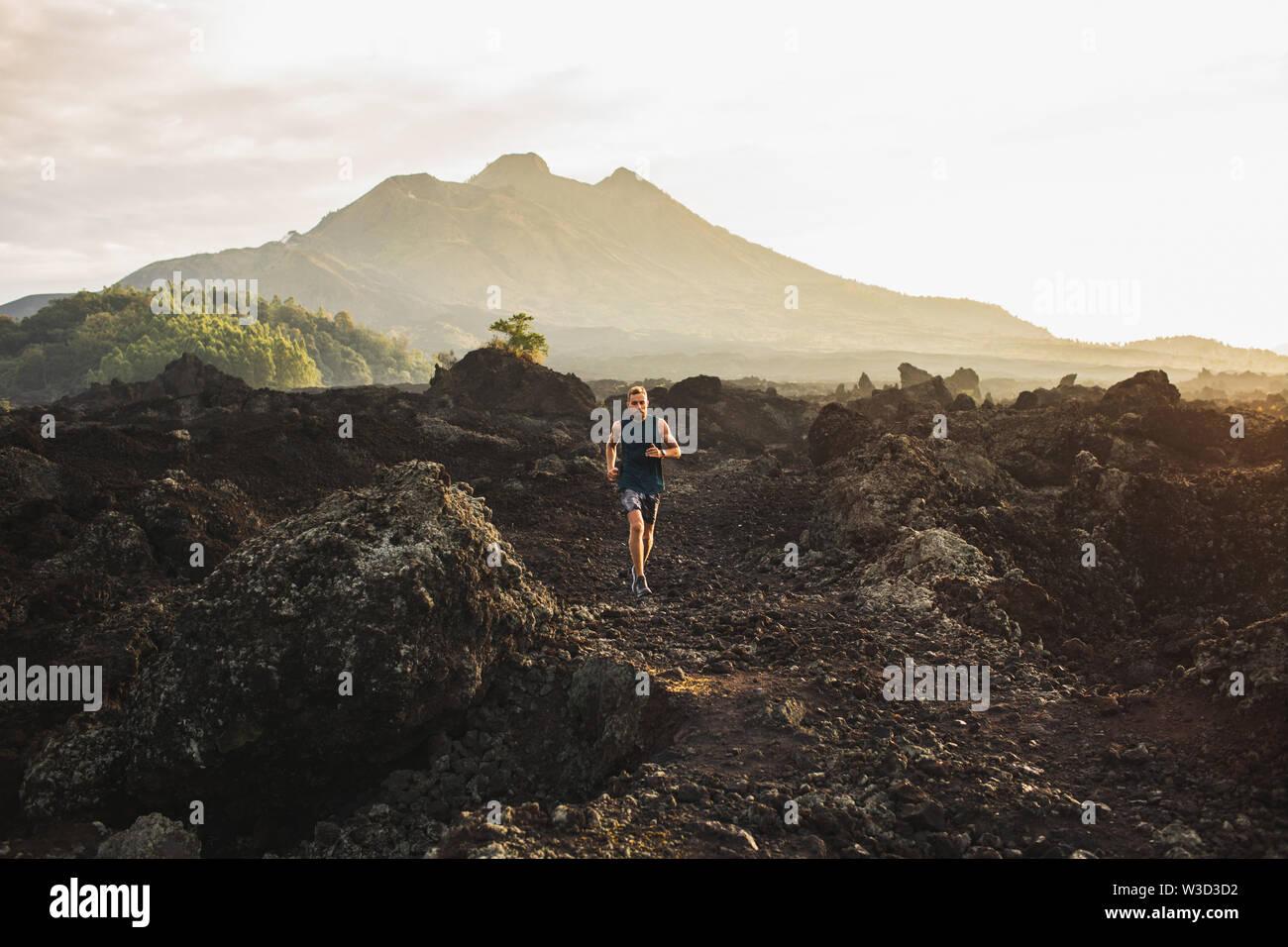 Jeune athlète homme trail running en montagne le matin. Amazing paysage volcanique du mont Batur Bali sur l'arrière-plan. Concept de vie sain. Banque D'Images