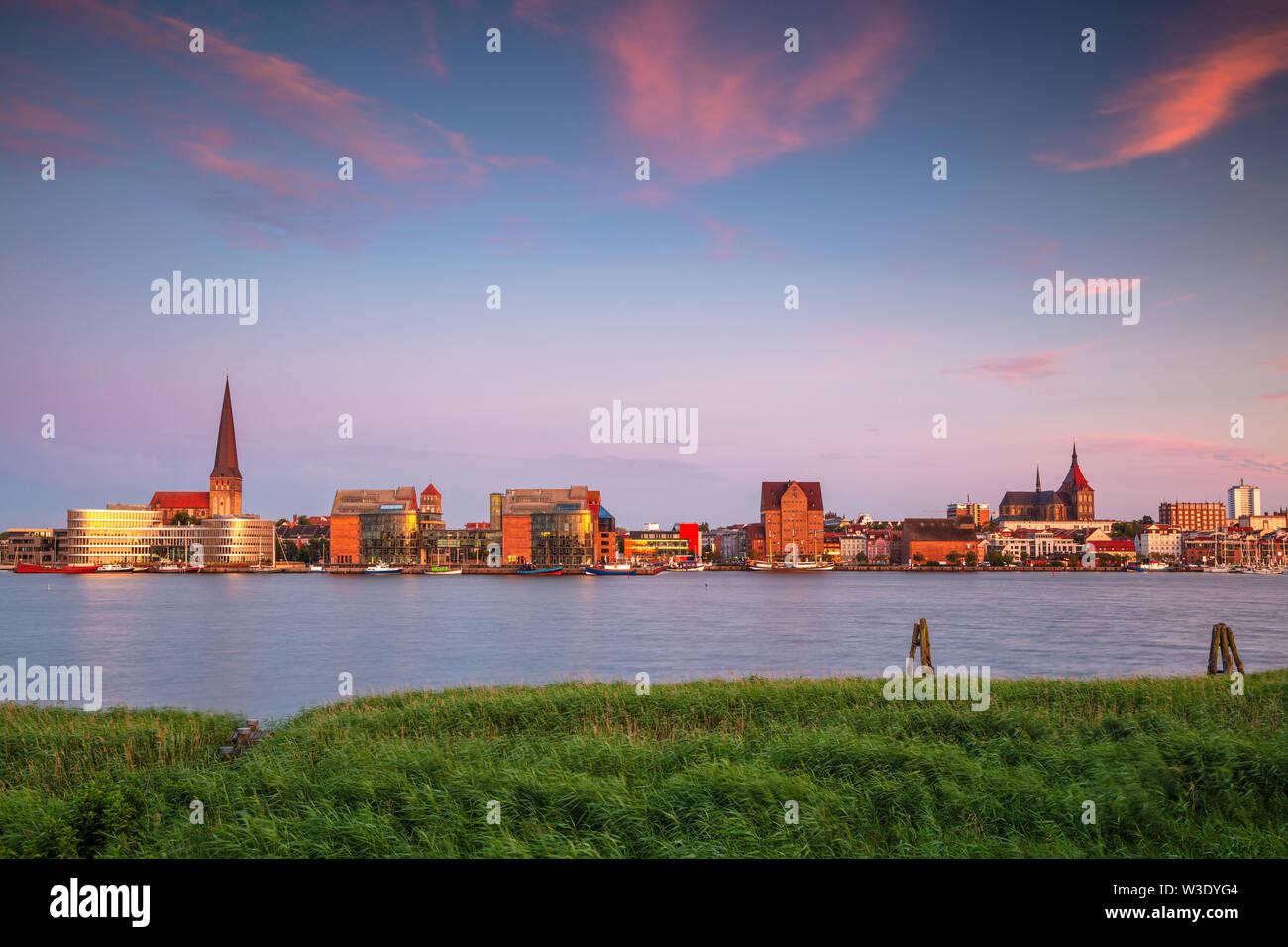 Rostock, Allemagne. Image cityscape du bord de la rivière Rostock avec l'église Saint-Pierre au coucher du soleil de l'été. Banque D'Images