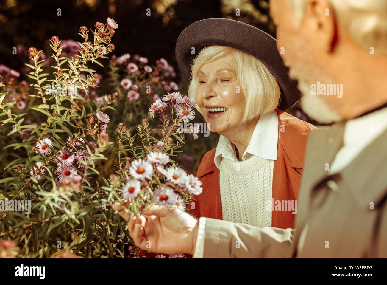 Vieille dame souriant à l'inhalation de belles fleurs. Photo Stock